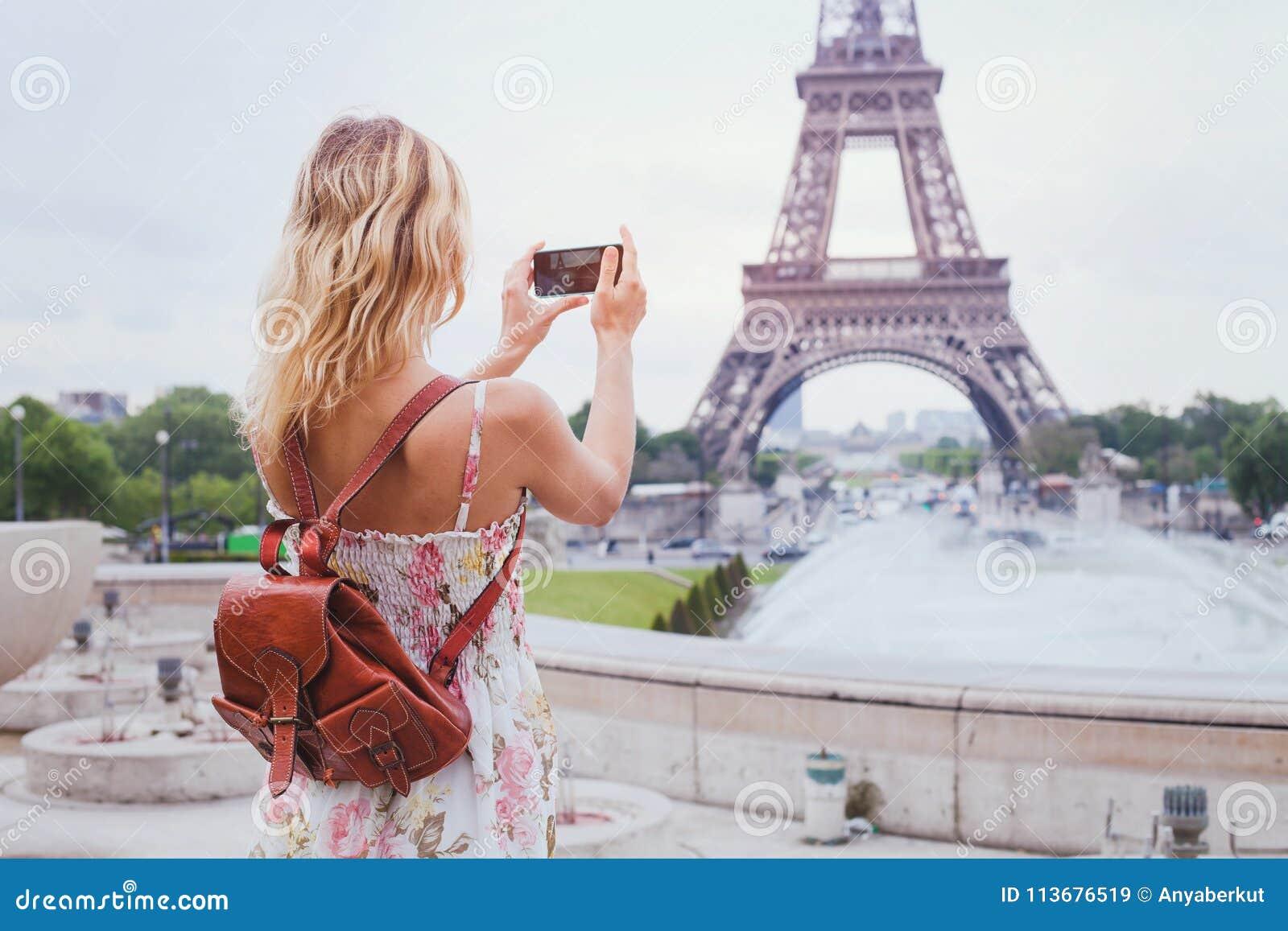 Turista que toma a foto da torre Eiffel em Paris
