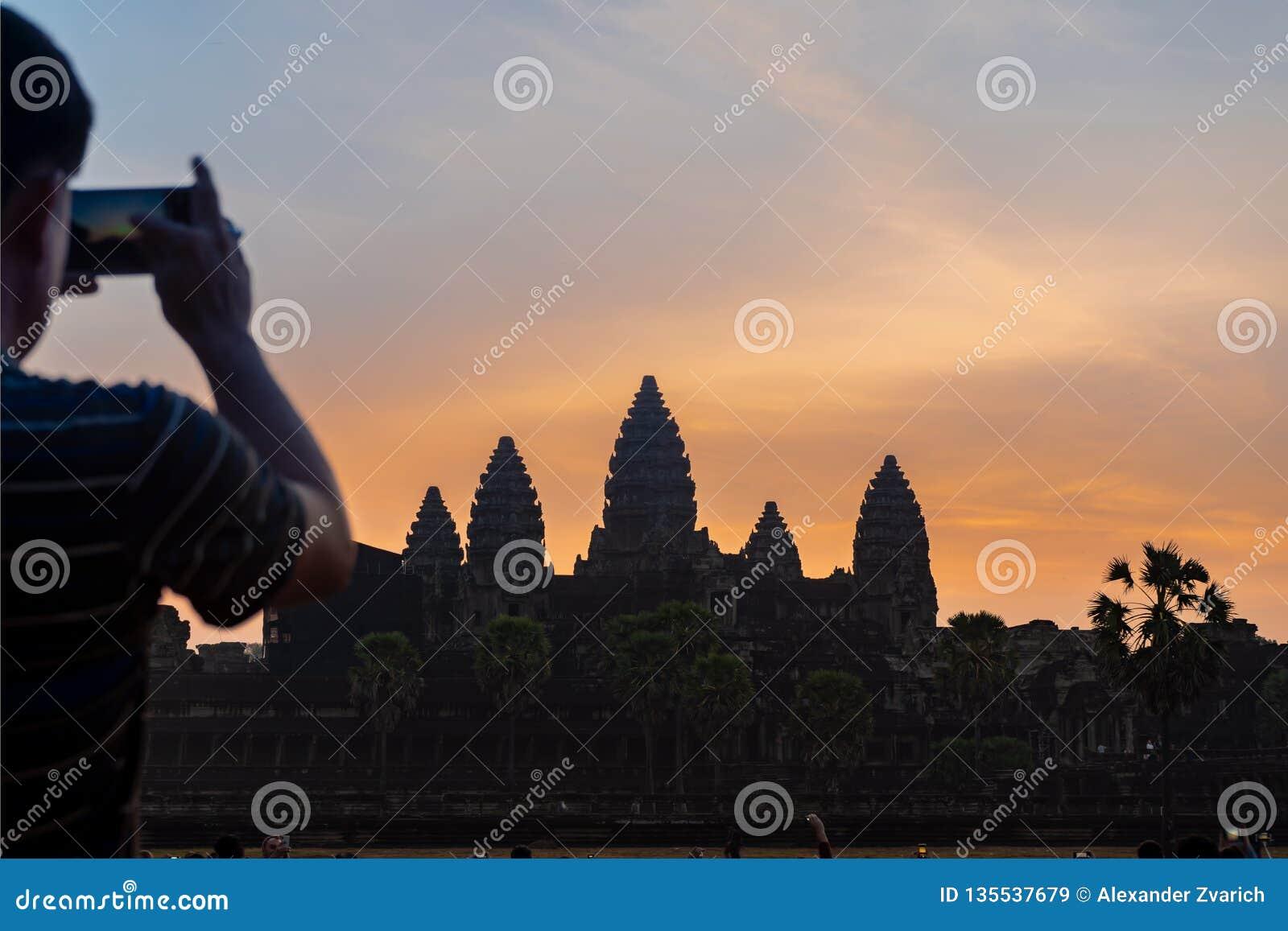 Turista que toma a foto de Angkor Wat no nascer do sol