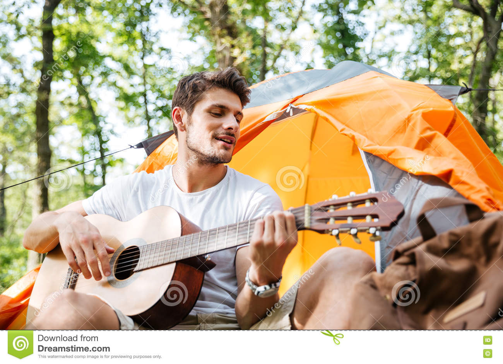 Turista sonriente del hombre joven que sienta y que toca la guitarra en bosque