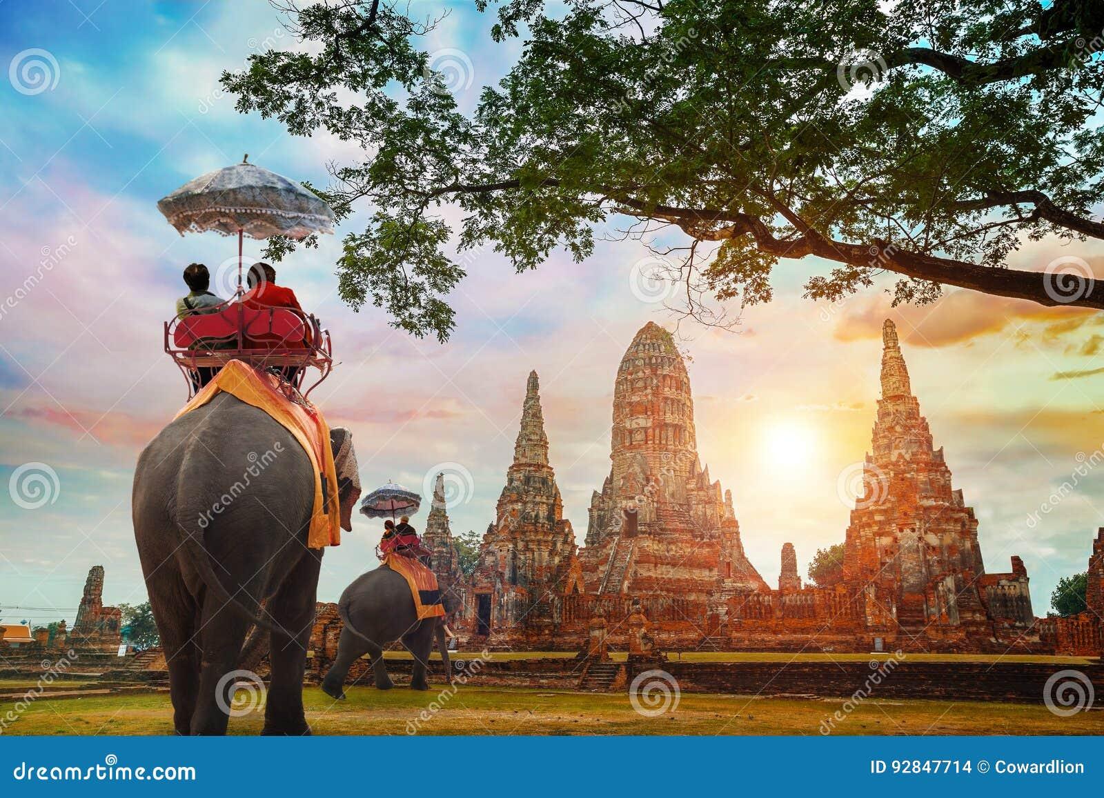 Turistas com os elefantes no templo de Wat Chaiwatthanaram no parque histórico de Ayuthaya, Tailândia