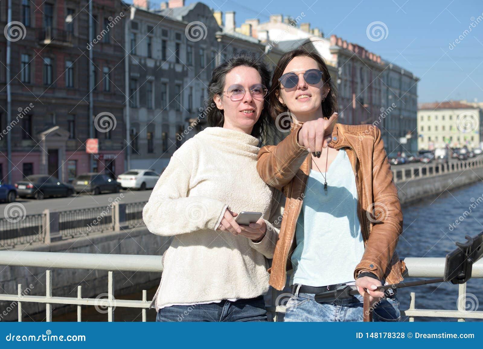 Turistas de las se?oras jovenes en selfies de la toma de St Petersburg Rusia en un puente de madera en el centro de ciudad hist?r