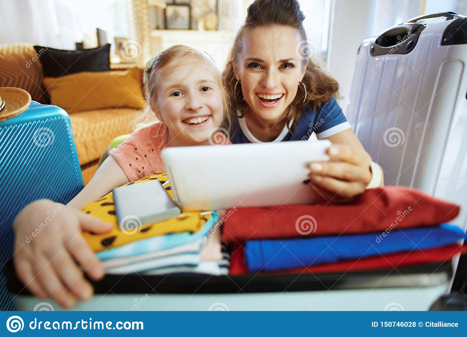 Turistas de sorriso da mãe e da filha que compram voos em linha