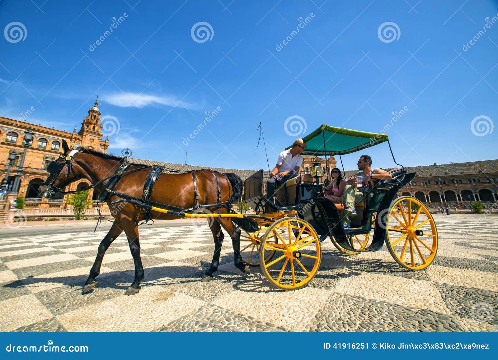 Turistas del carro del caballo que dan un paseo a través de la plaza de España en Sevilla