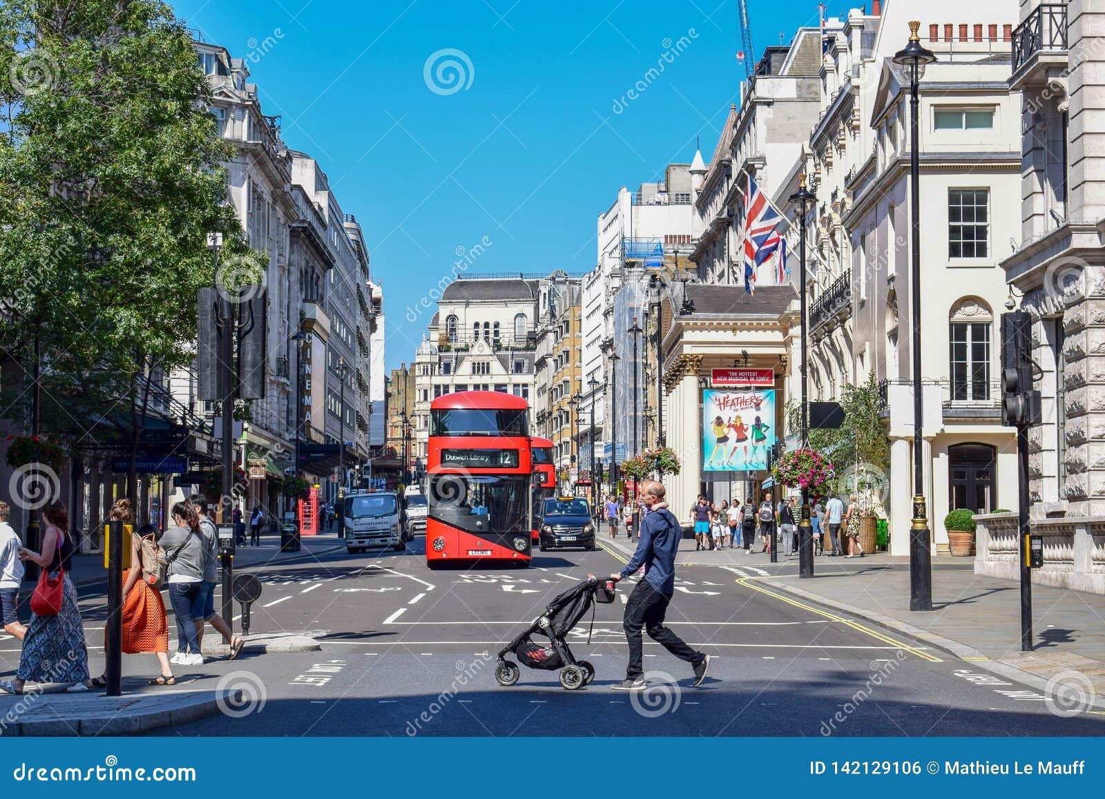 Turistas e ônibus de dois andares na rua de Londres em Sunny Day