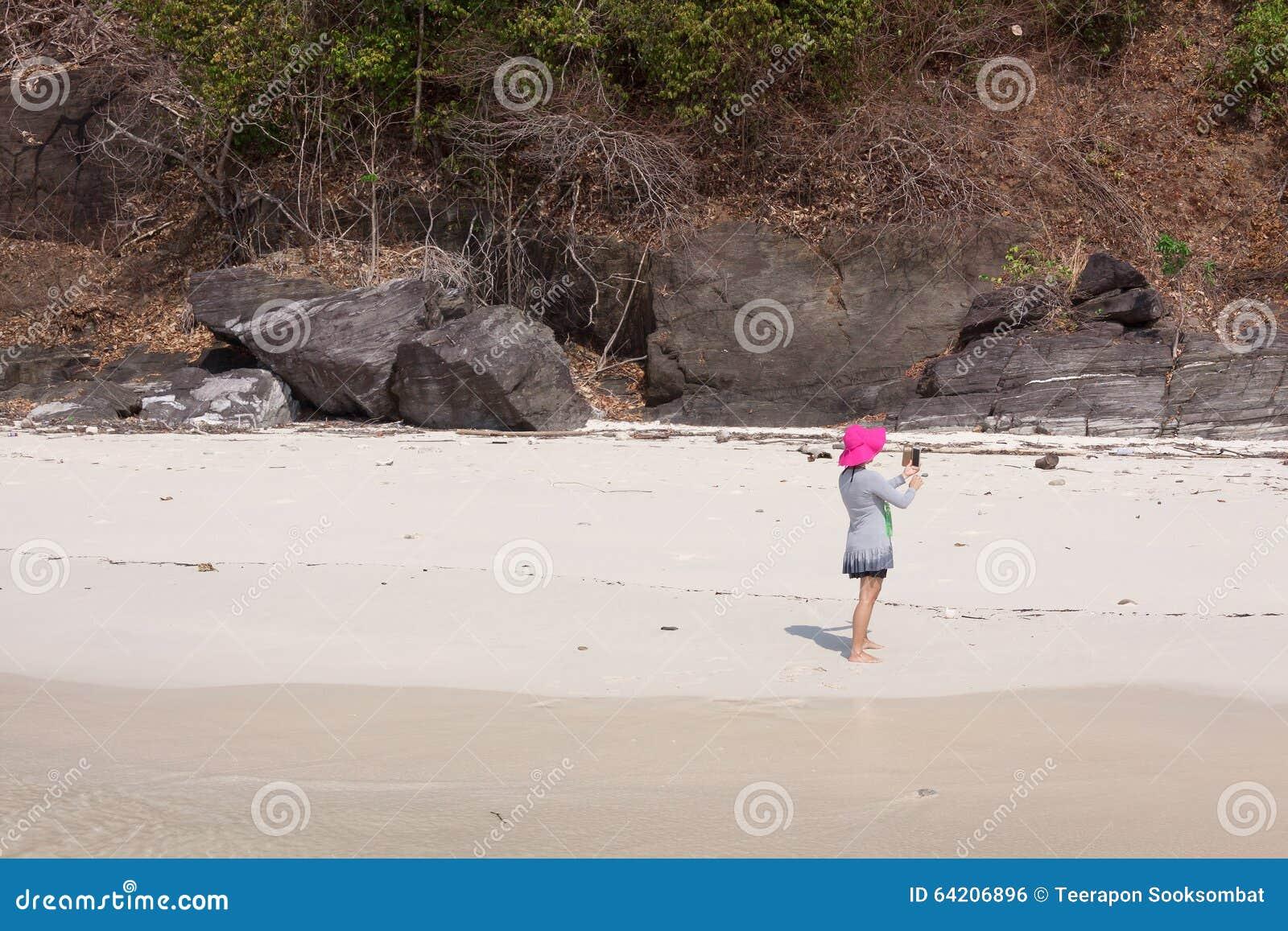 Turistas en la playa blanca de la arena