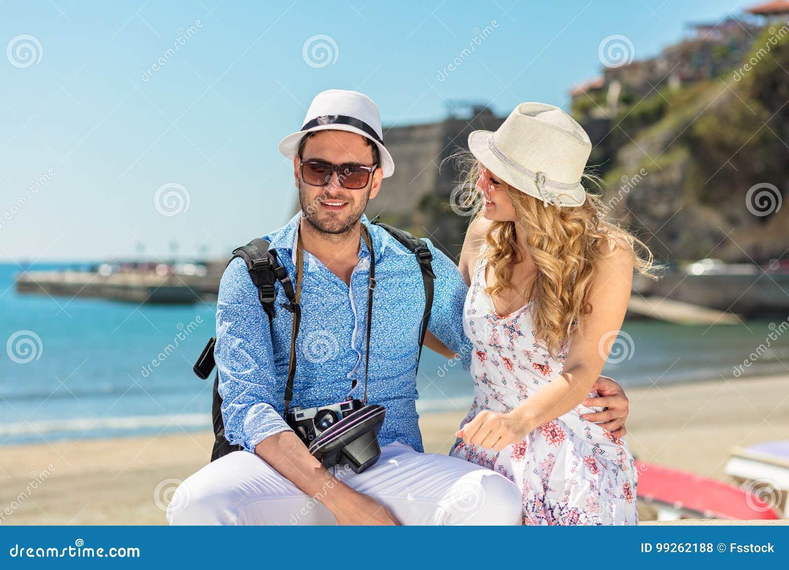 Turistas felizes que descansam no doc ao explorar a cidade junto