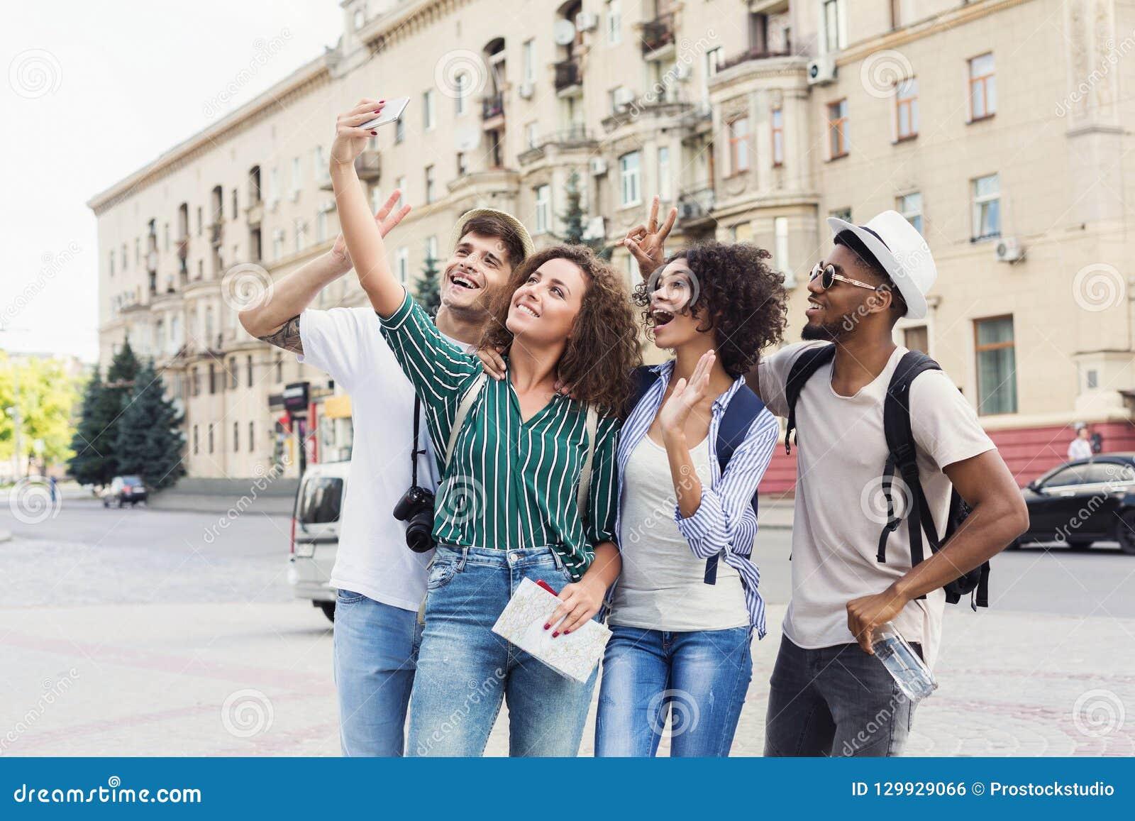 Turistas multirraciais dos amigos que fazem o selfie na cidade