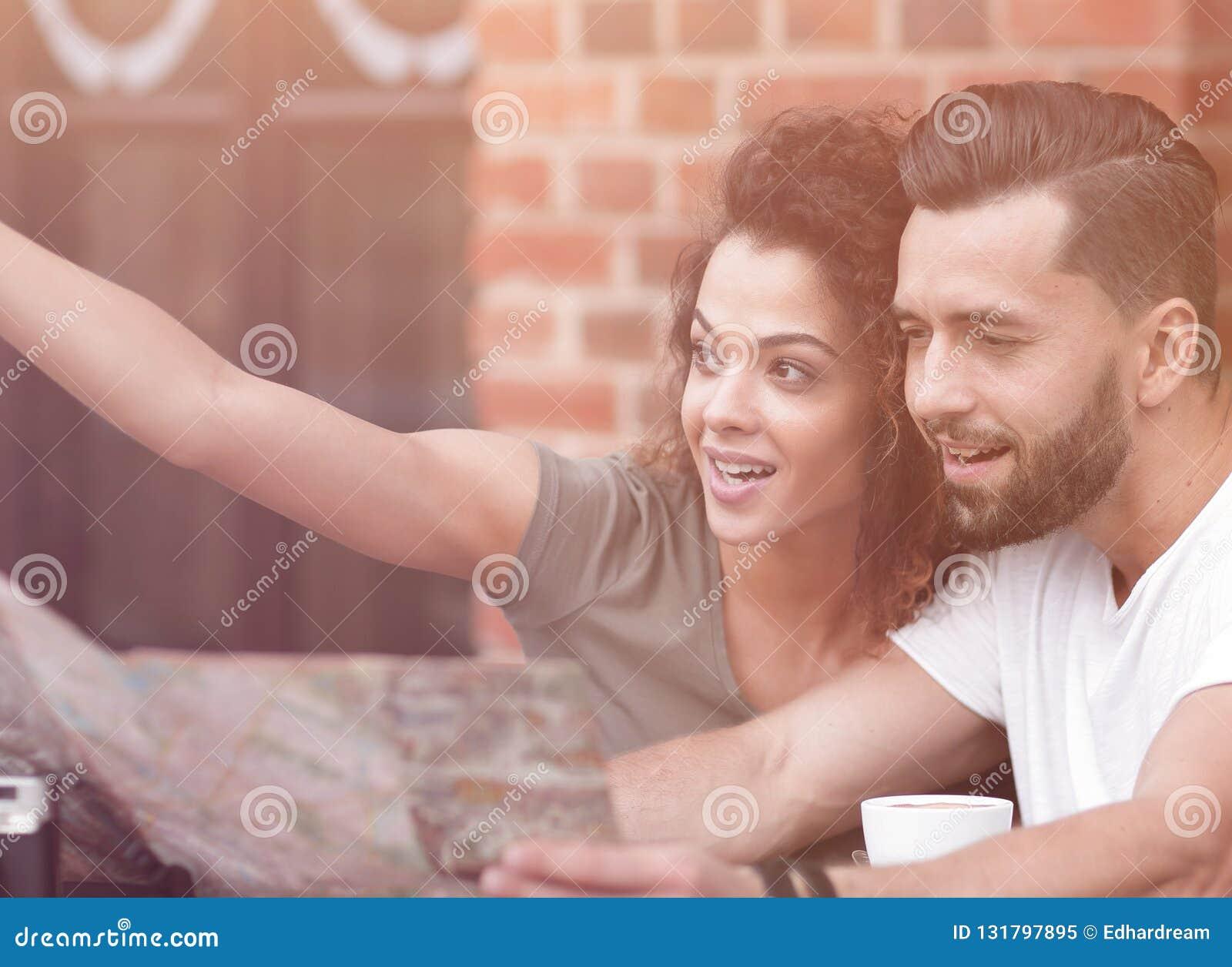 Turistas novos que comem o café no café e que leem o mapa