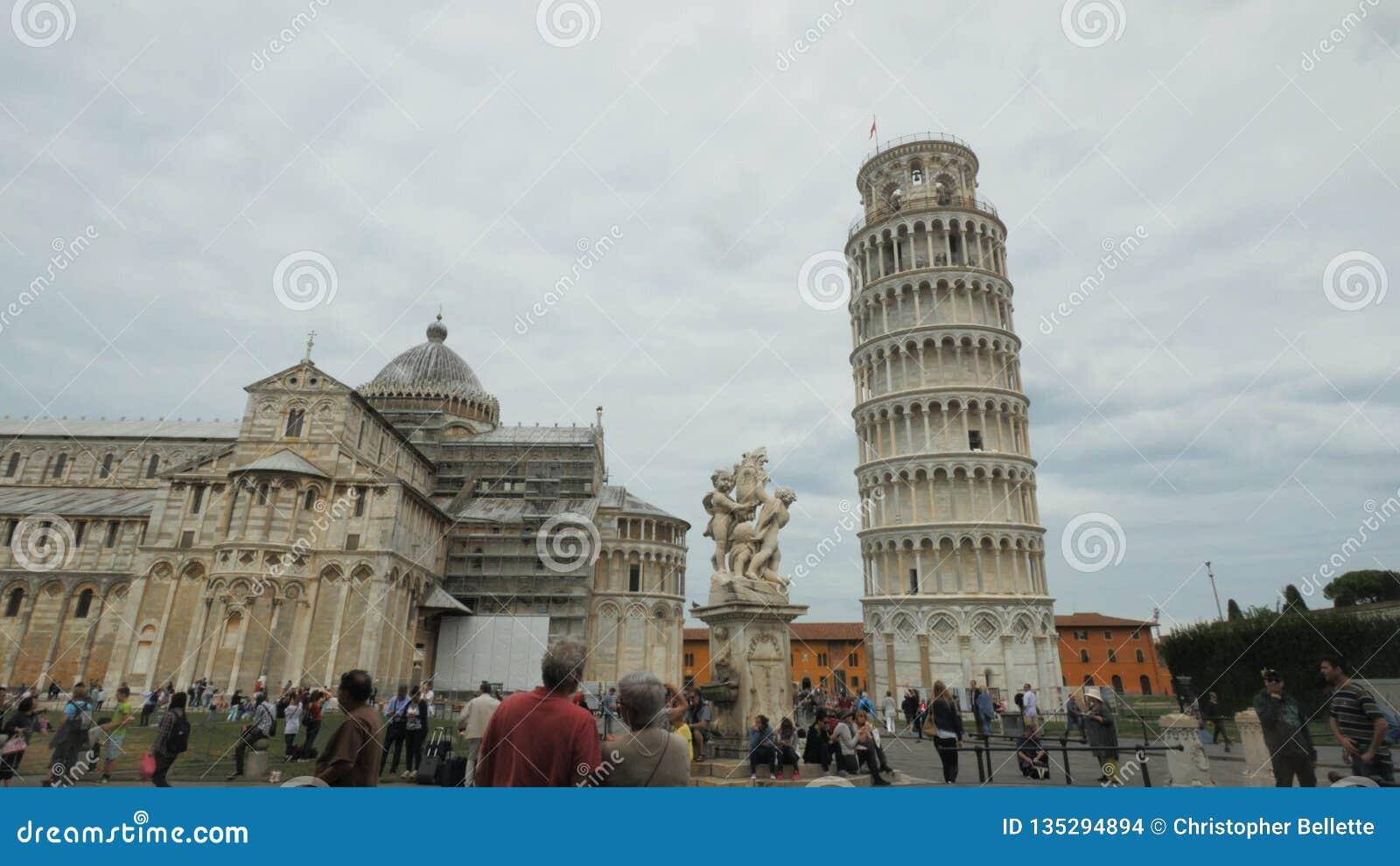 Turistas que admiram a torre inclinada famosa de pisa filme