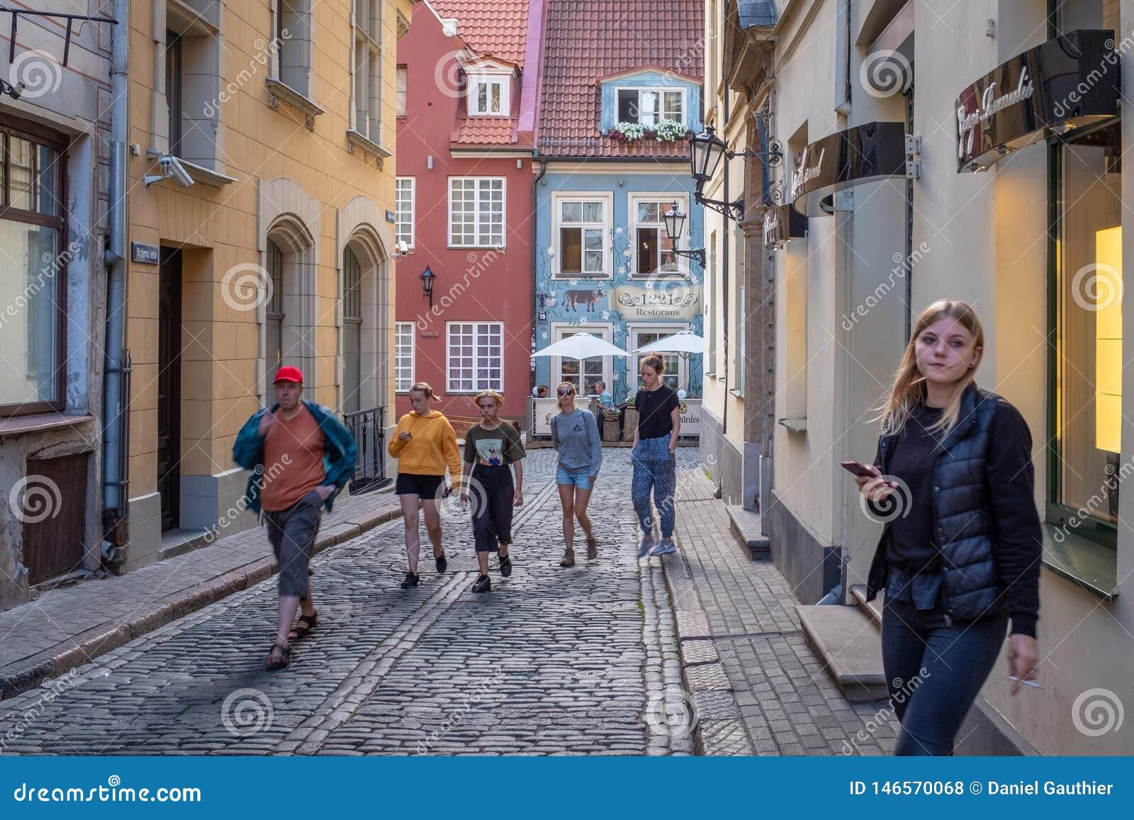 Turistas que andam acima de uma rua estreita da cidade velha de Riga