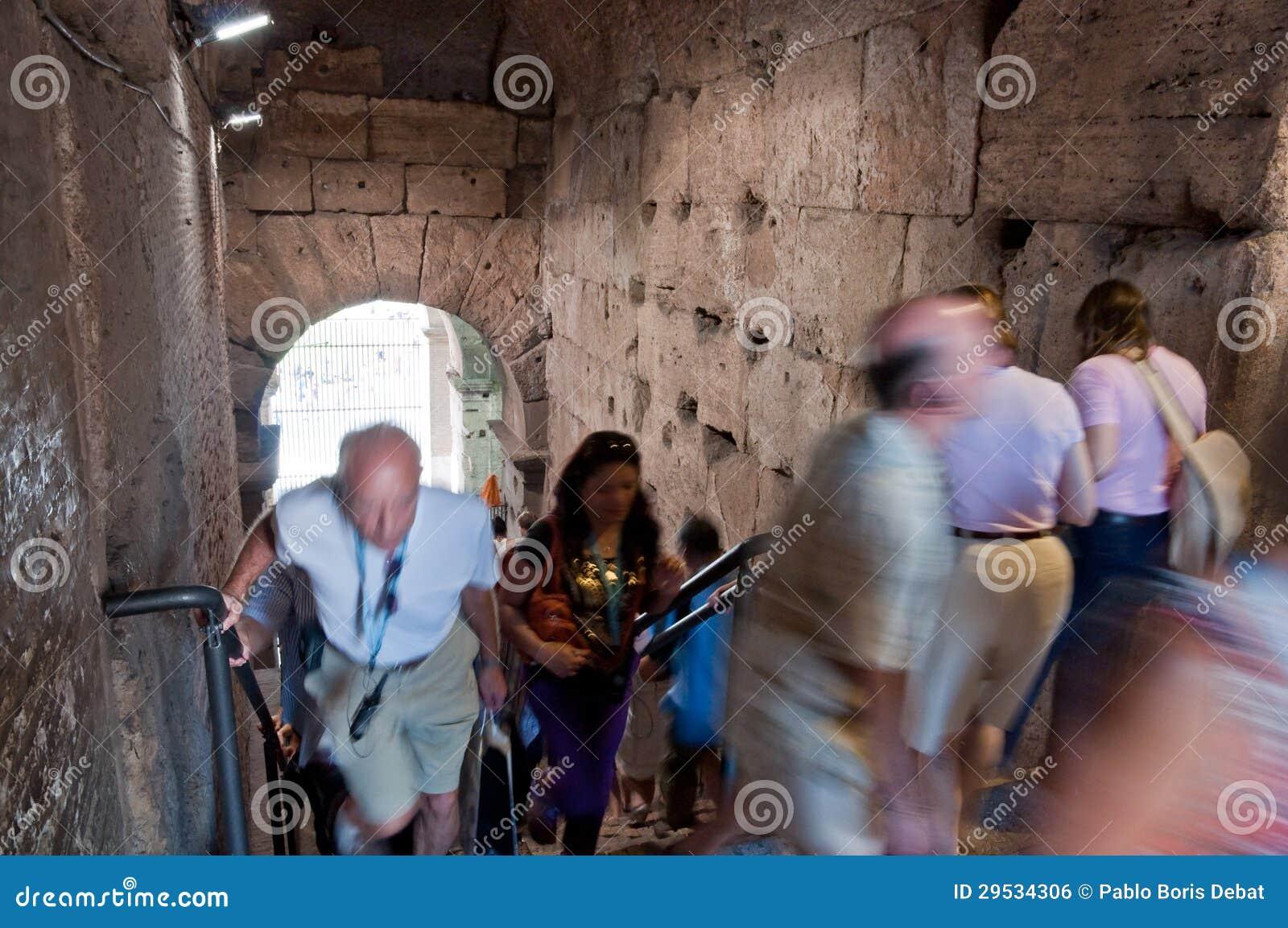 Turistas que andam dentro das escadas do colosseum em Roma