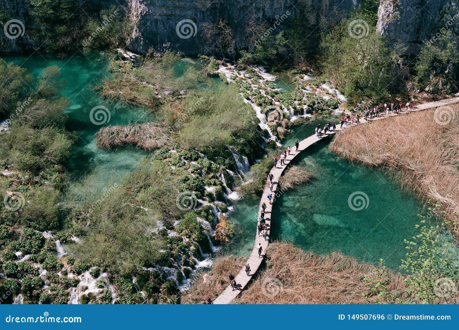 Turistas que caminan sobre el agua de la turquesa de los lagos Plitvice