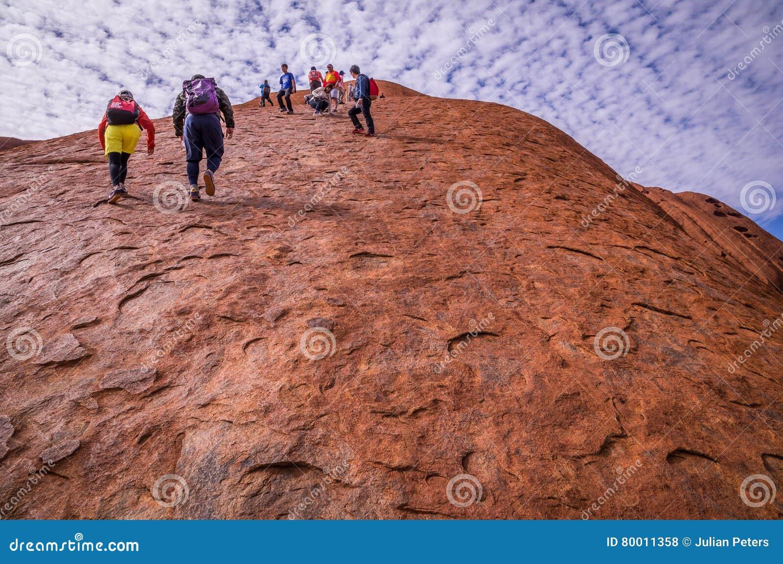 Turistas que escalam a rocha de Uluru Ayers