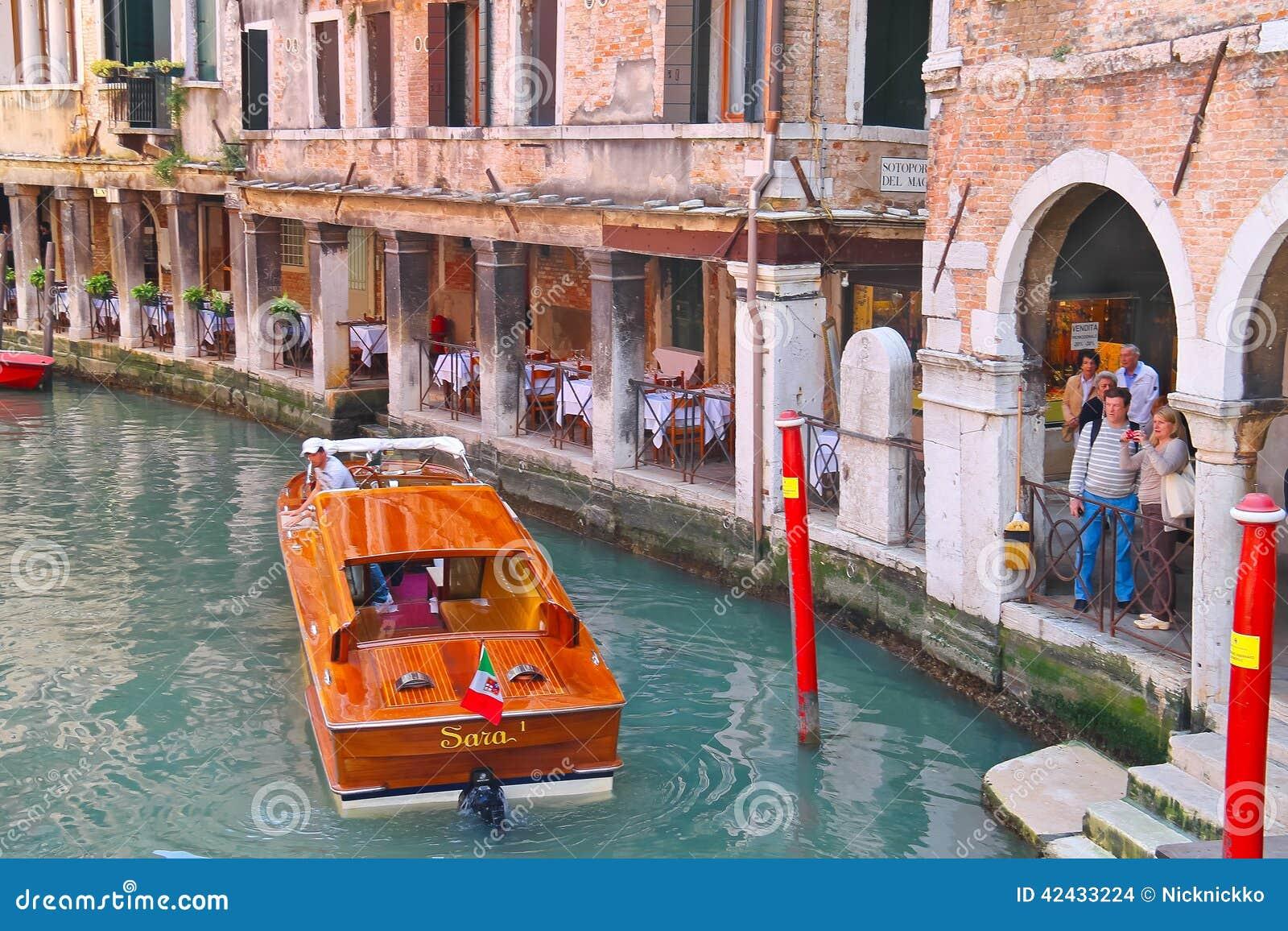 Turistas que esperan el aterrizaje en un barco de placer en Venecia, Italia