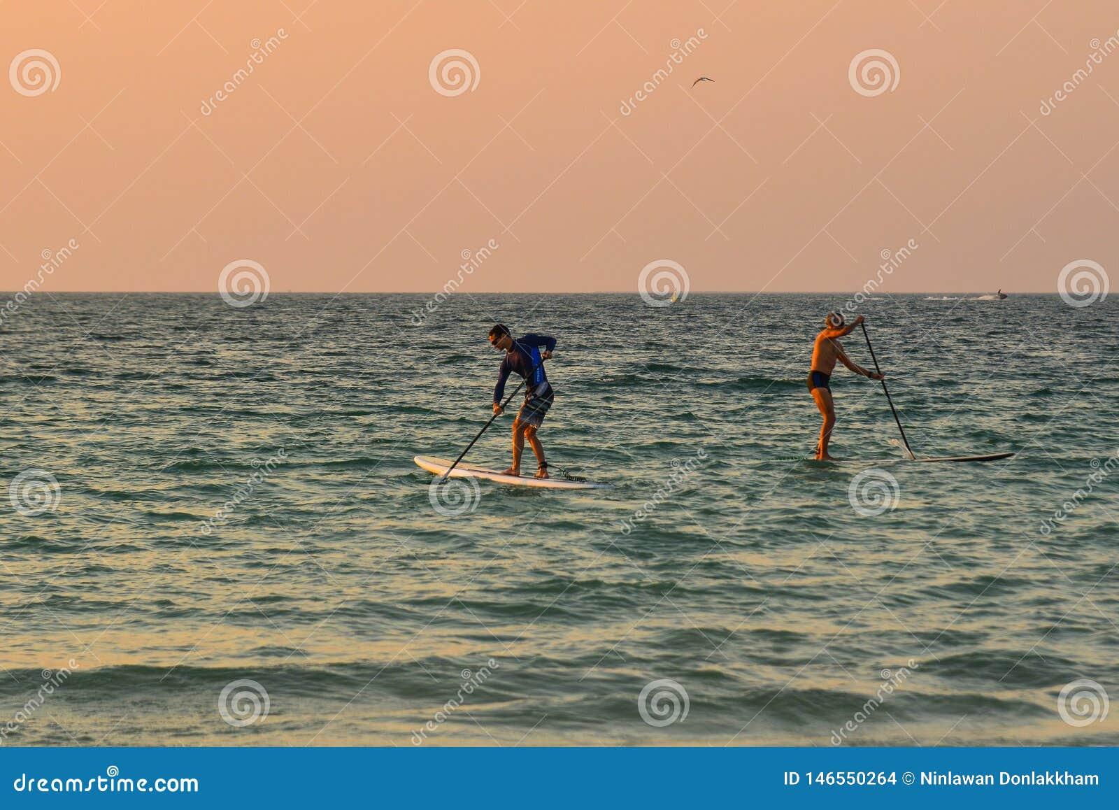 Turistas que kayaking no mar no por do sol