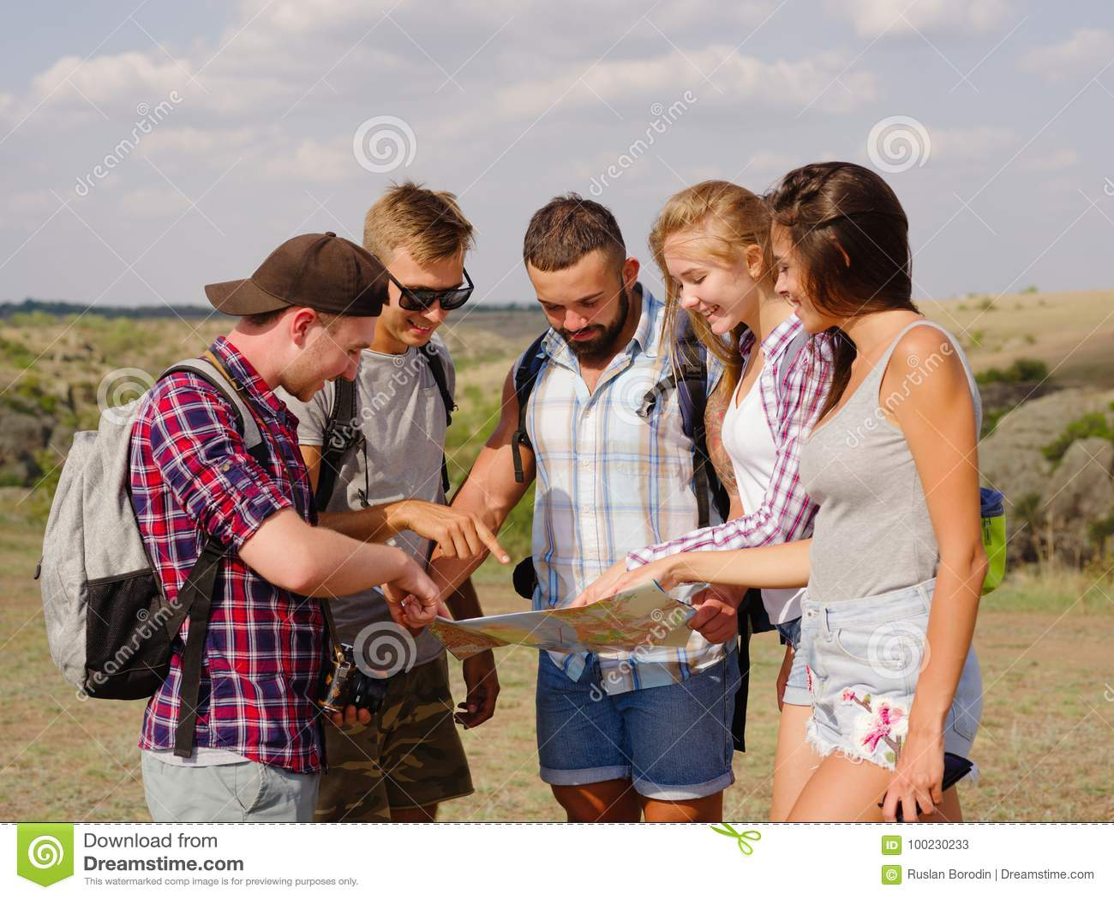 Turistas que miran una correspondencia Mapa de la demostración de la guía a los estudiantes que viajan en un fondo natural Concep