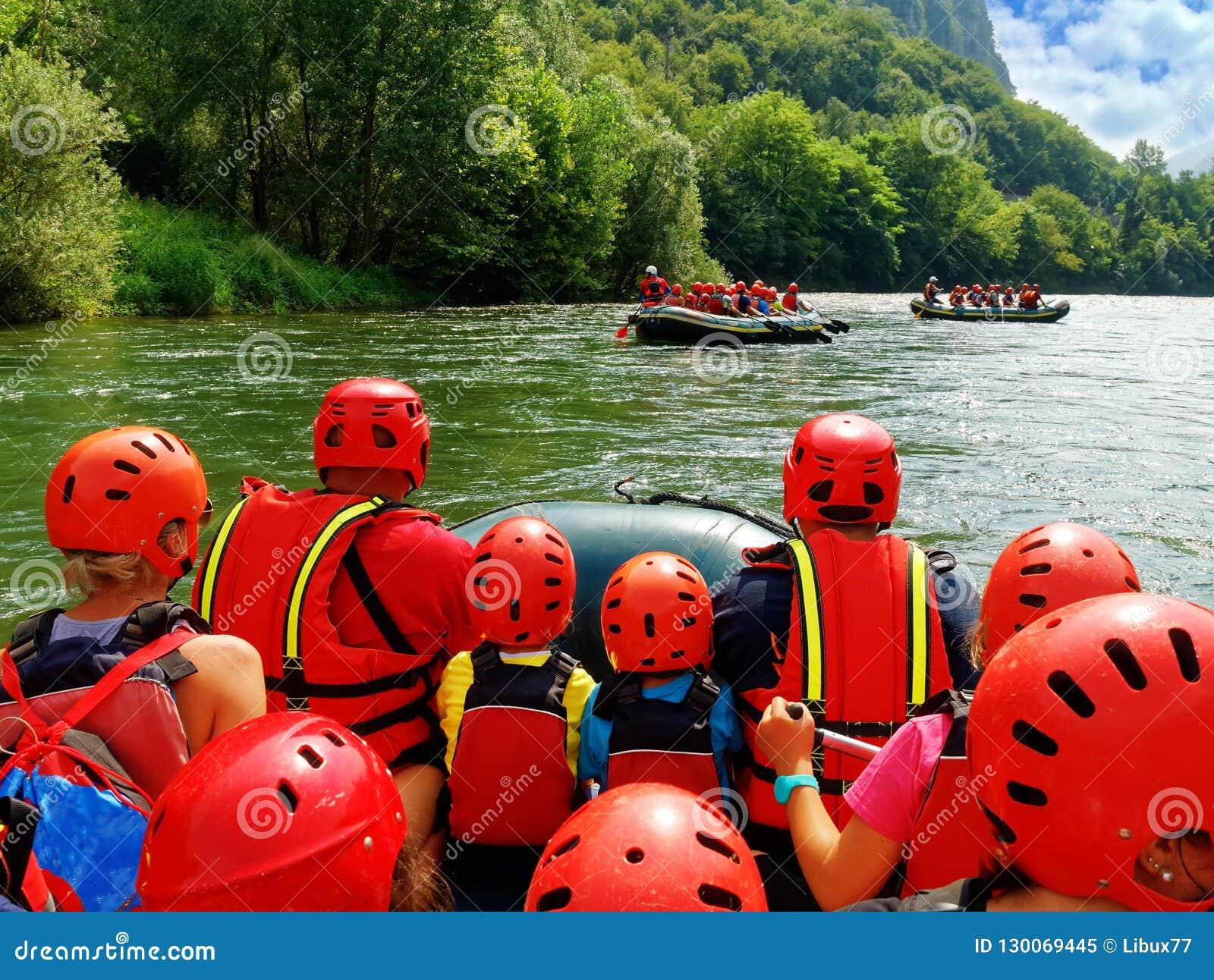 Turistas que se divierten que hace el agua que transporta el tiro del punto de vista en balsa