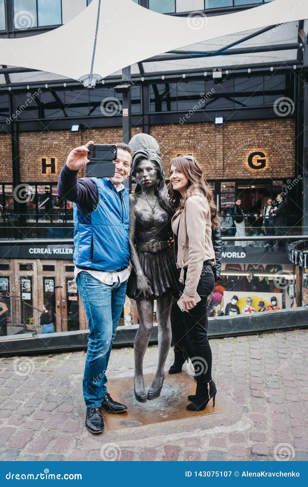 Turistas que tomam fotos com a estátua de Amy Winehouse em Camden, Londres, Reino Unido