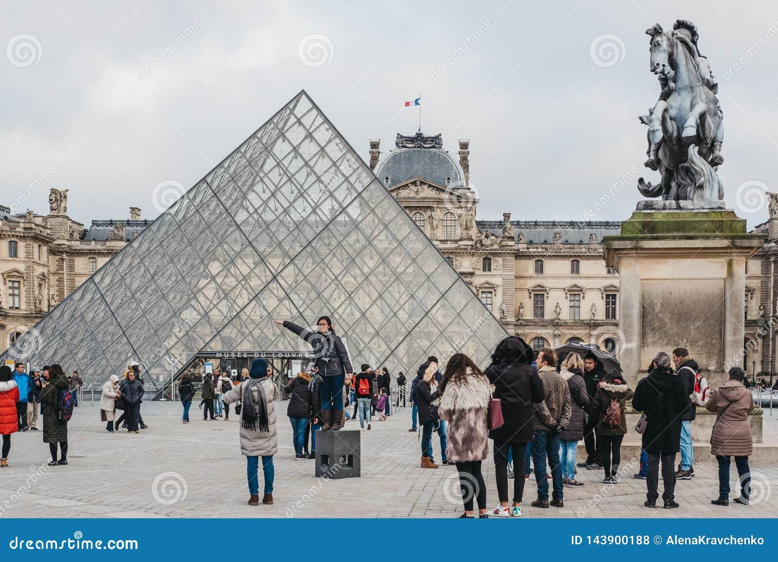 Turistas que tomam imagens na parte dianteira no museu do Louvre em Paris, França
