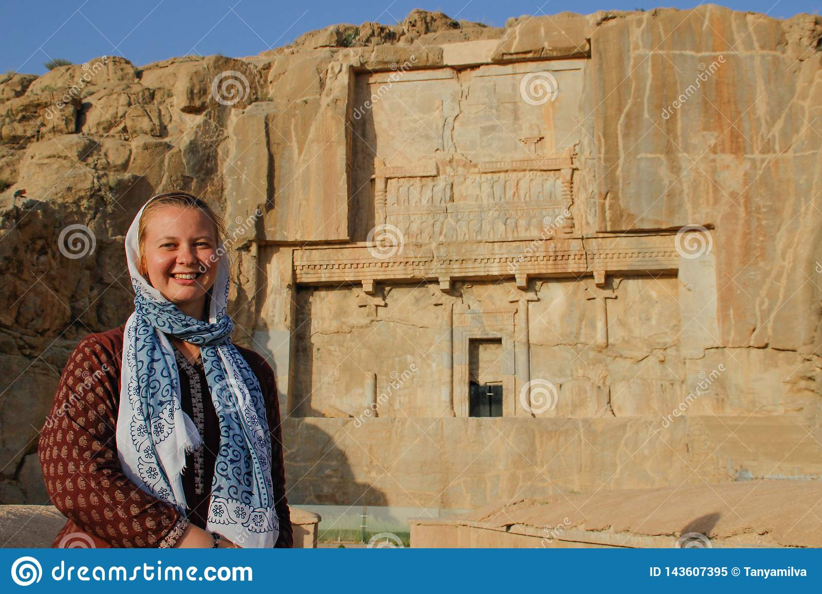Turisten för den unga kvinnan med ett täckt huvud står på bakgrunden av de berömda basrelieferna av daghuvudstaden av Persia Iran