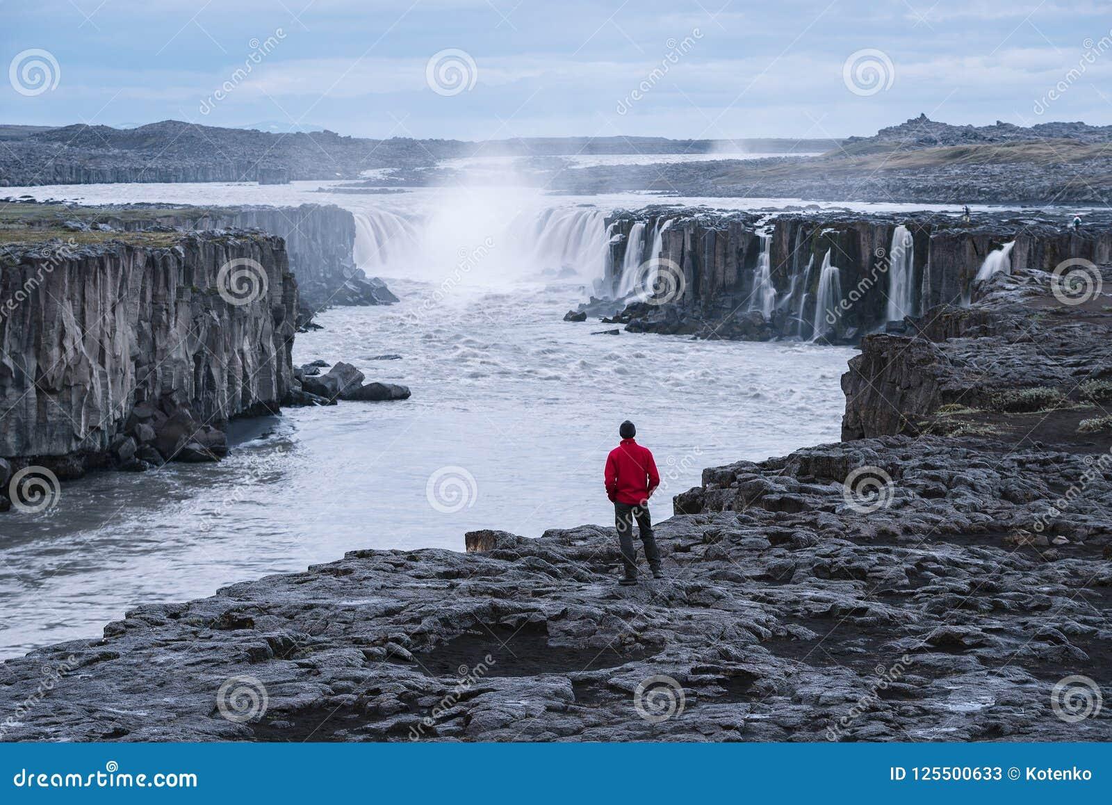 Turisten i ett rött omslag ser den Selfoss vattenfallet