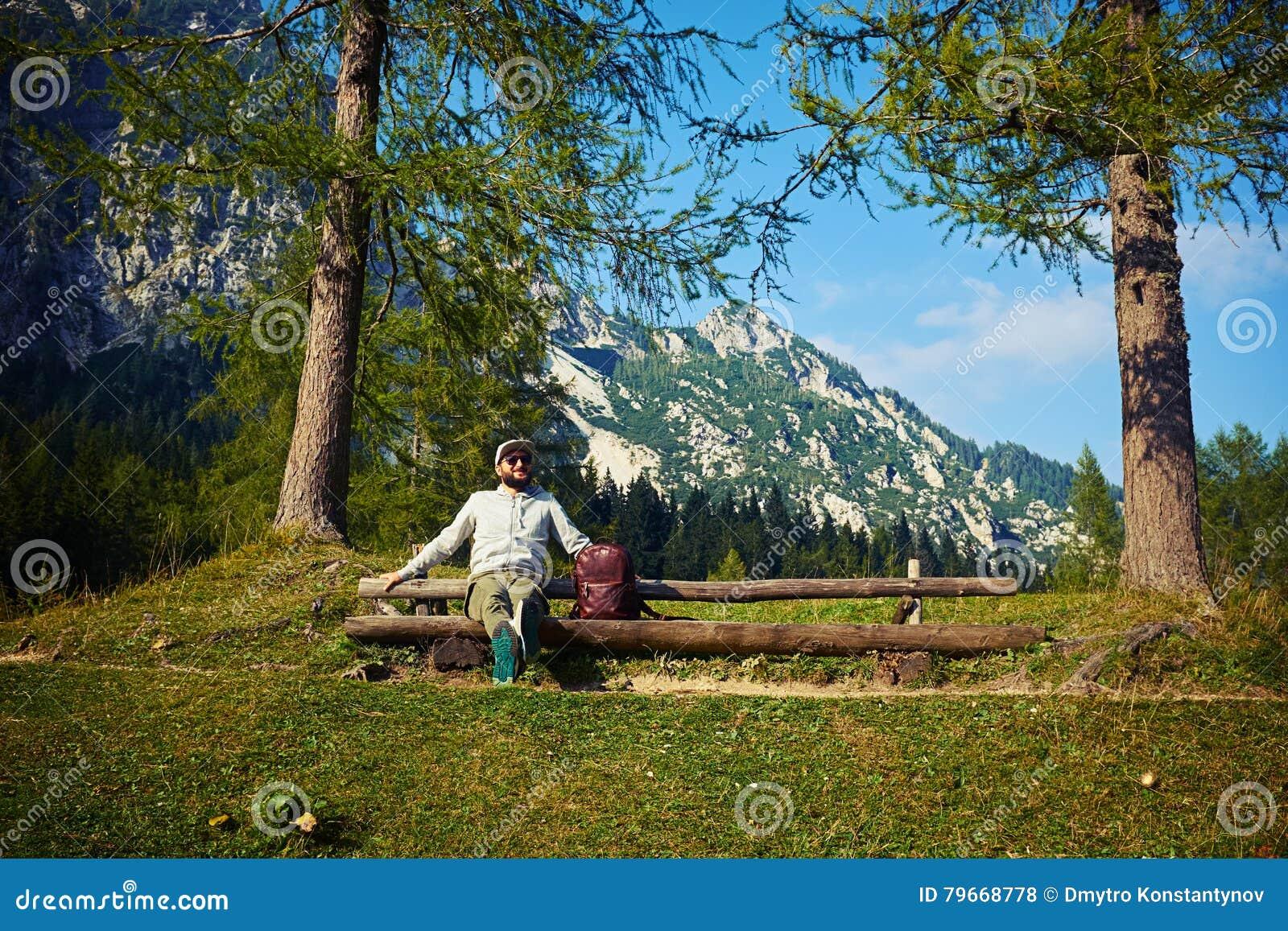 Turisten sitter på bänken, når han har klättrat berget
