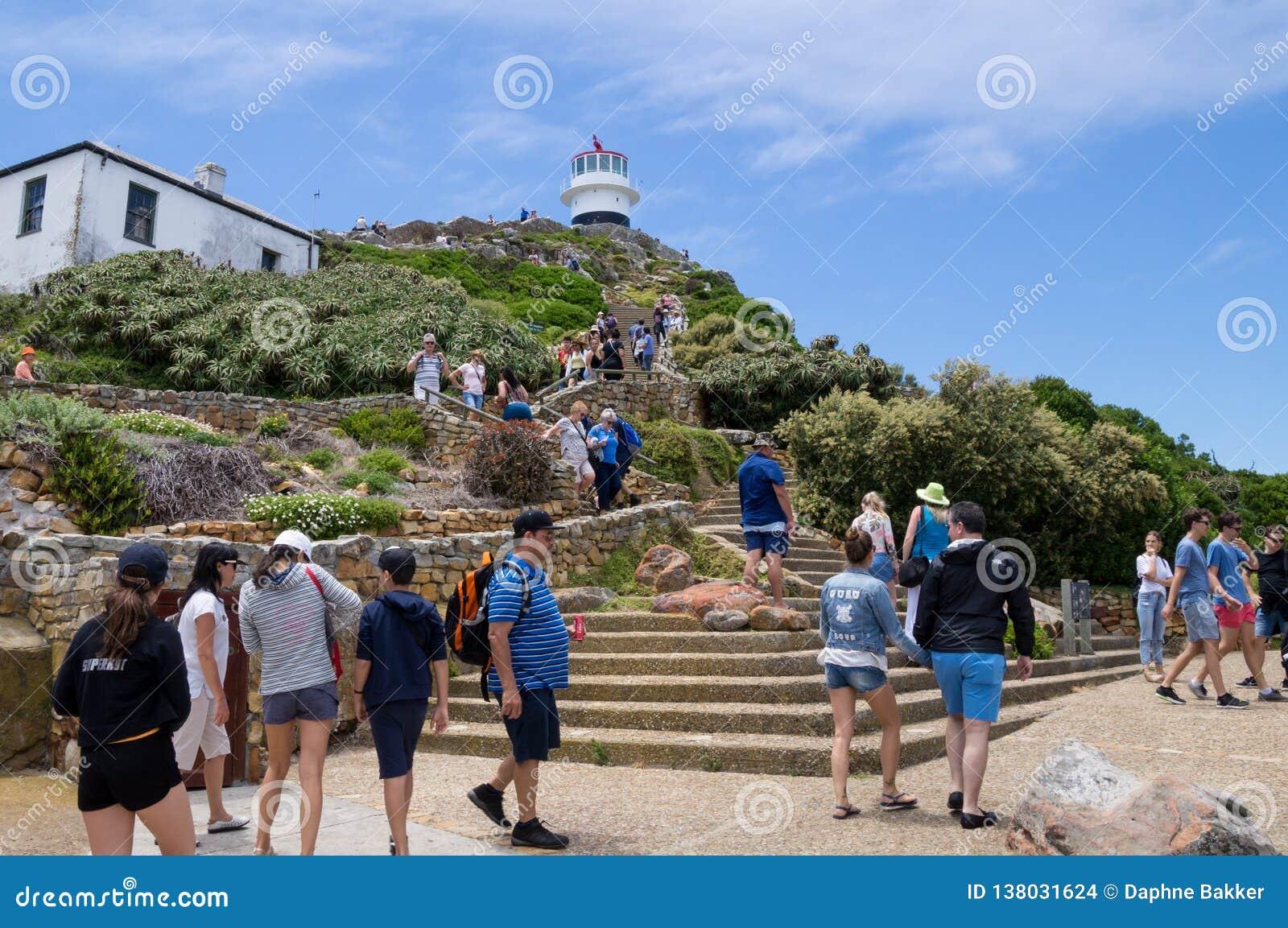 Turister som överst fotvandrar till fyren av Capepoint