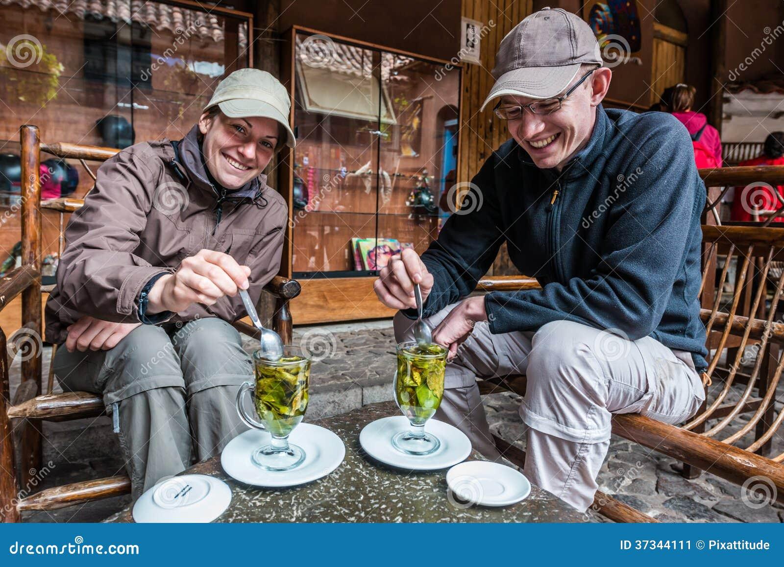 Turister som dricker cocateperuanen Anderna Pisac Peru