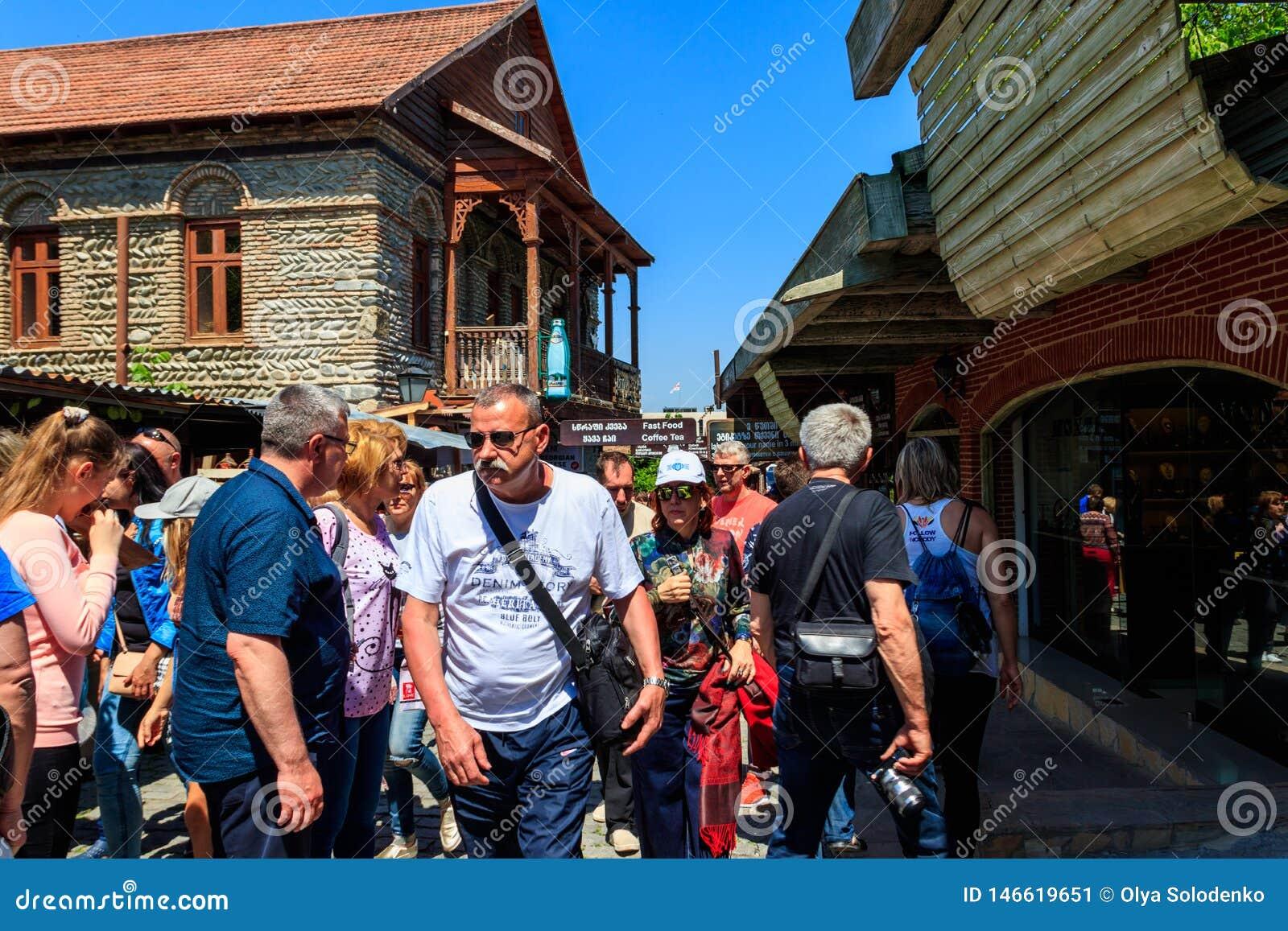 Turister som går på gatan med gåvasouvenir, shoppar i den historiska staden av Mtskheta