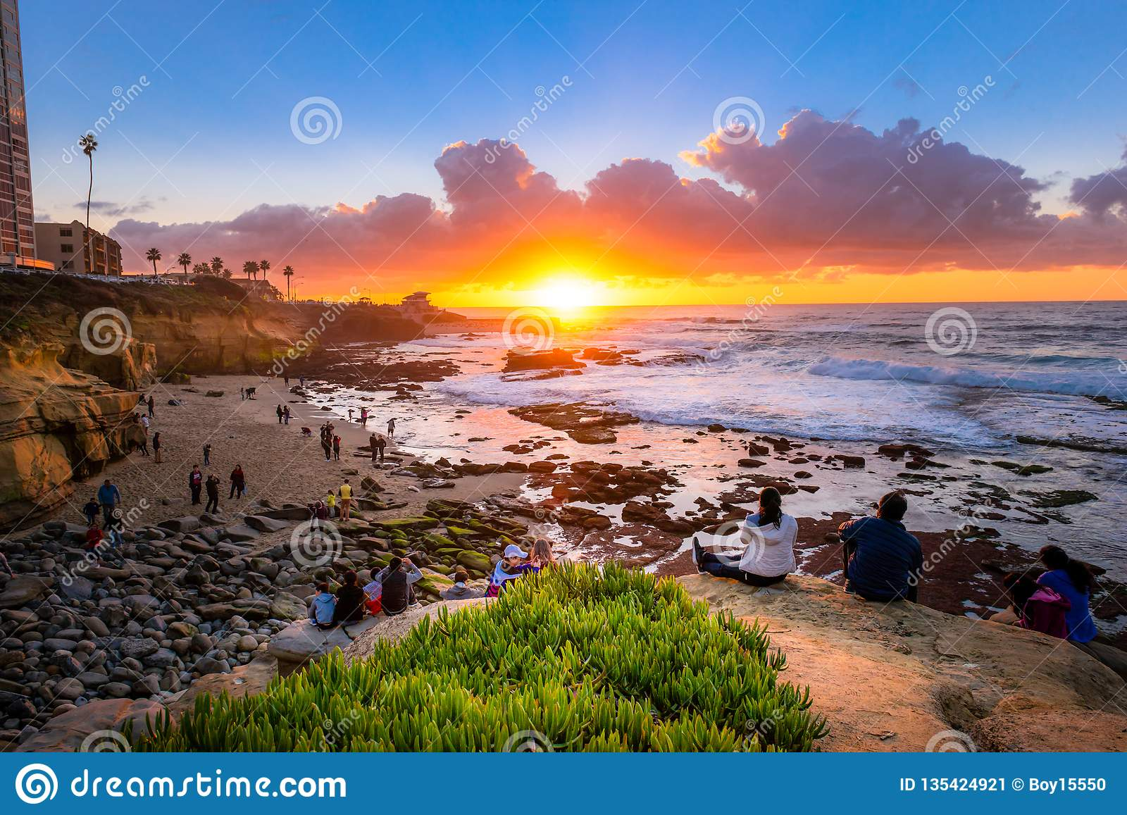Turister som håller ögonen på den beautifal solnedgången på La Jolla
