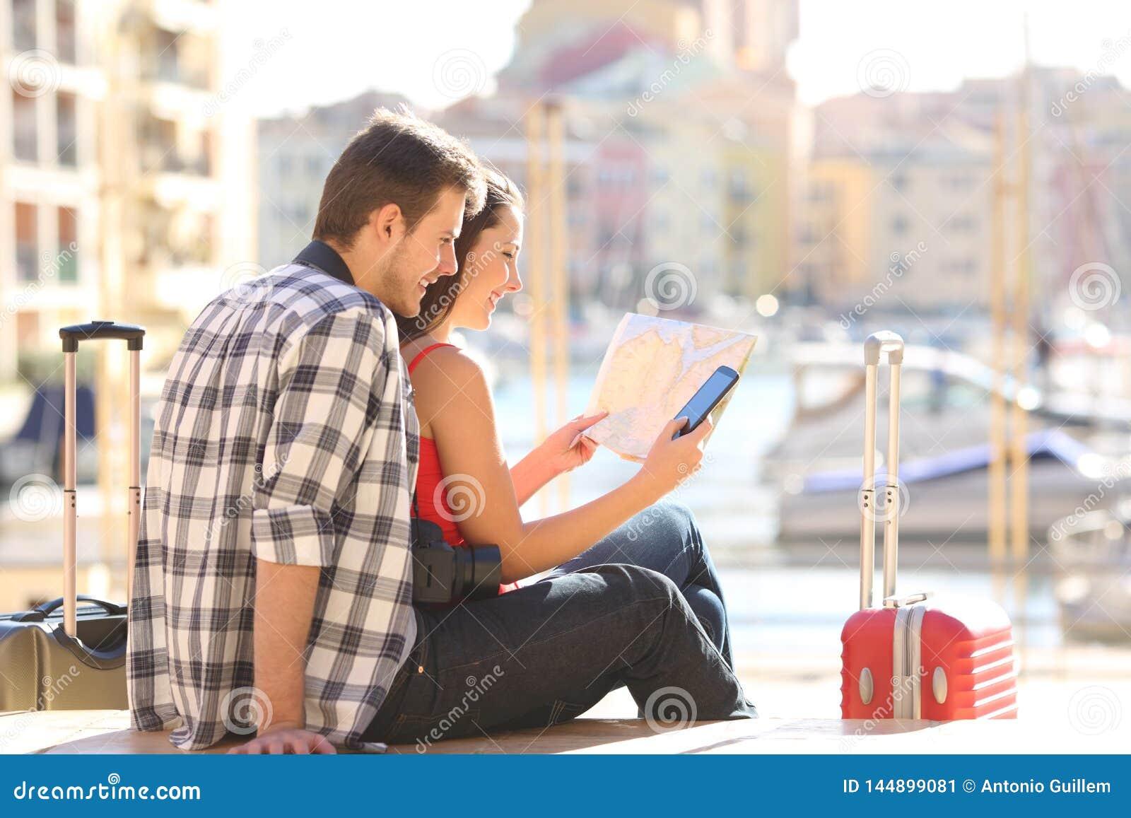 Turister som kontrollerar översikten och den smarta telefonen på ferie