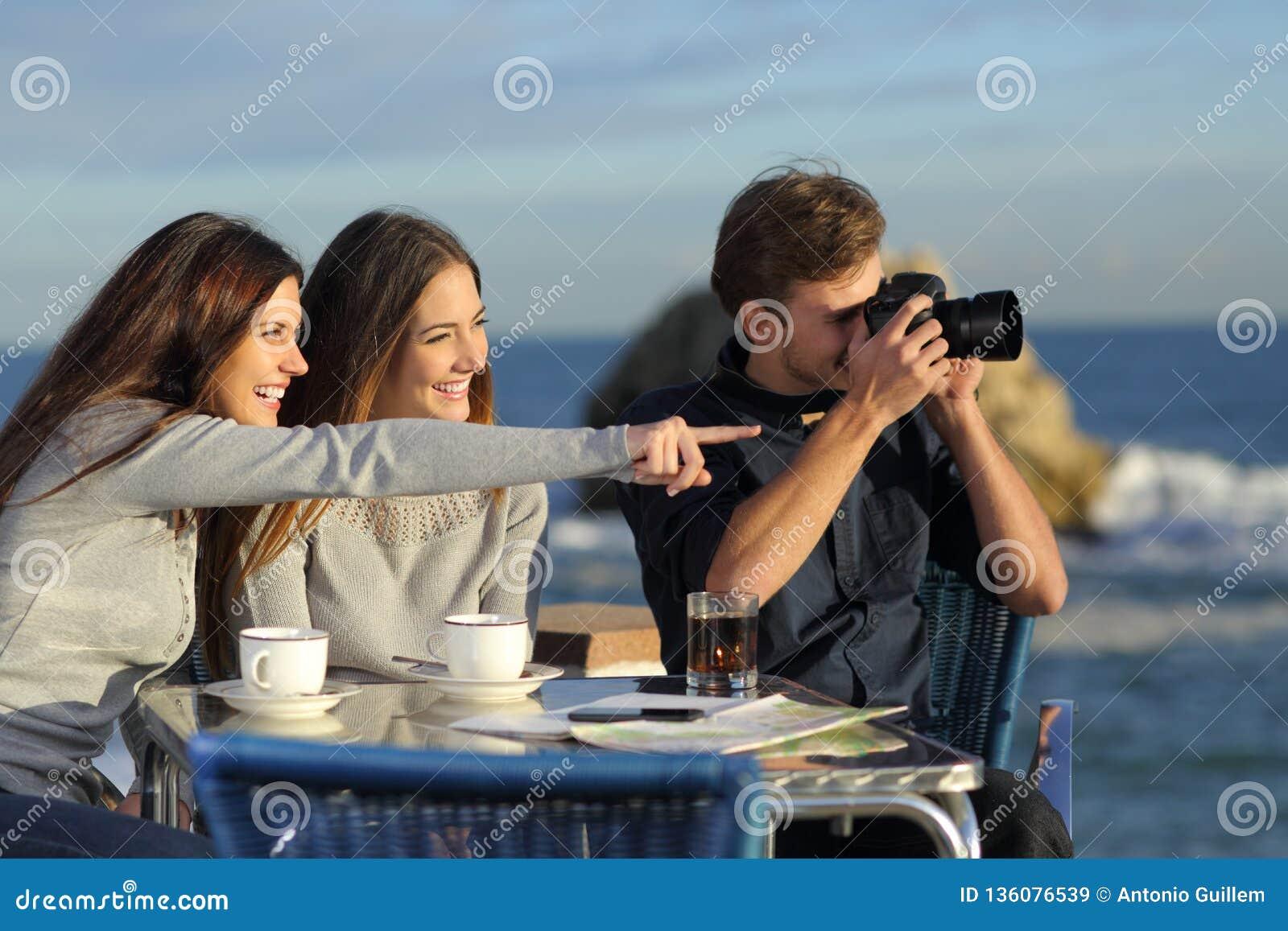 Turister som tar foto från en coffee shop
