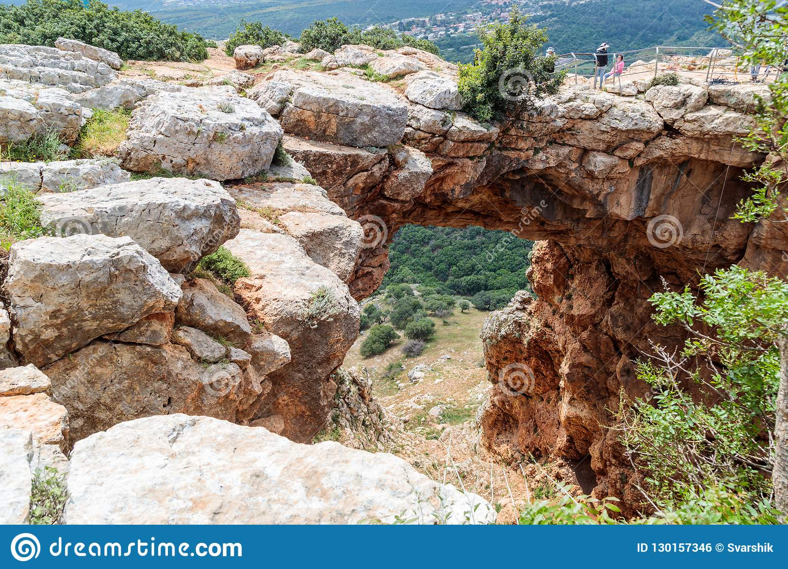 Turister står och ser den Keshet grottan - den forntida naturliga kalkstenbågen som spänner över restna av en grund grotta med at