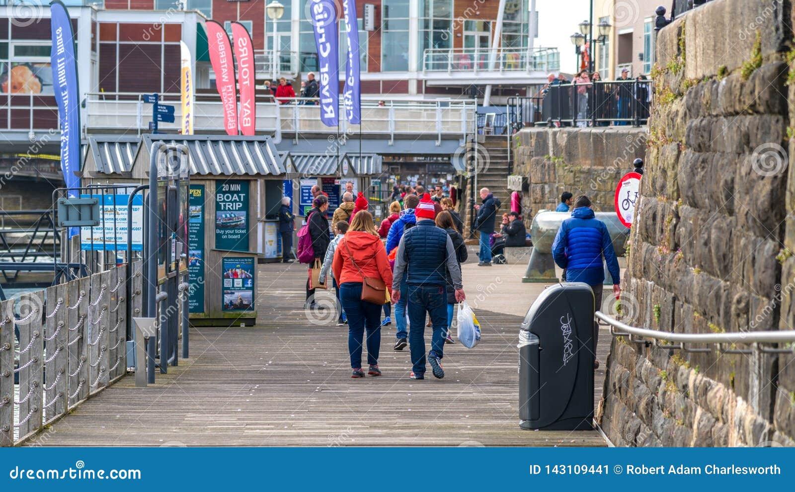 Turisti sulla banchina alla baia di Cardiff