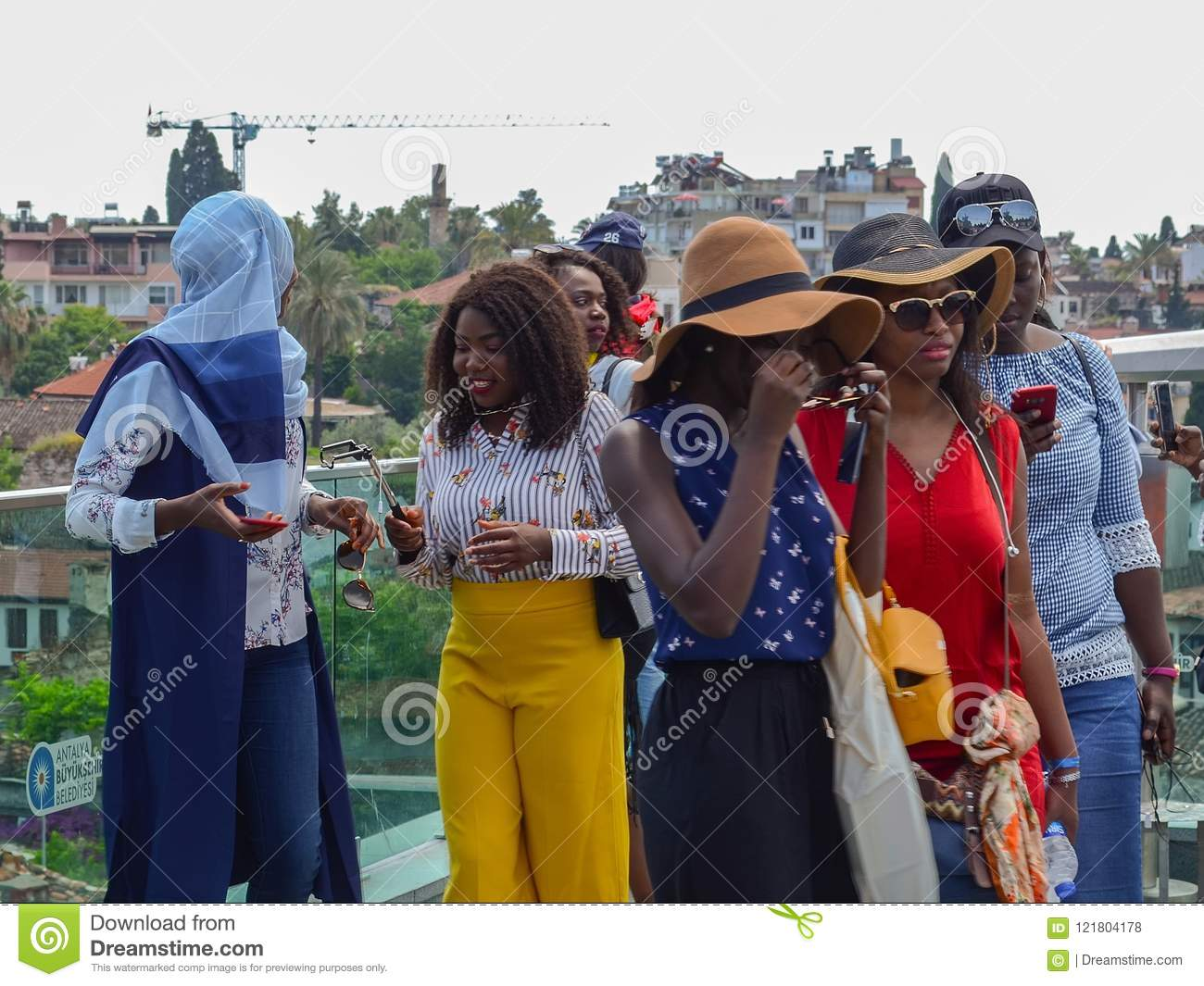 Turkey, Antalya, May 10, 2018. Group of young African women in bright clothes on the viewing platform in the old city inspecting t