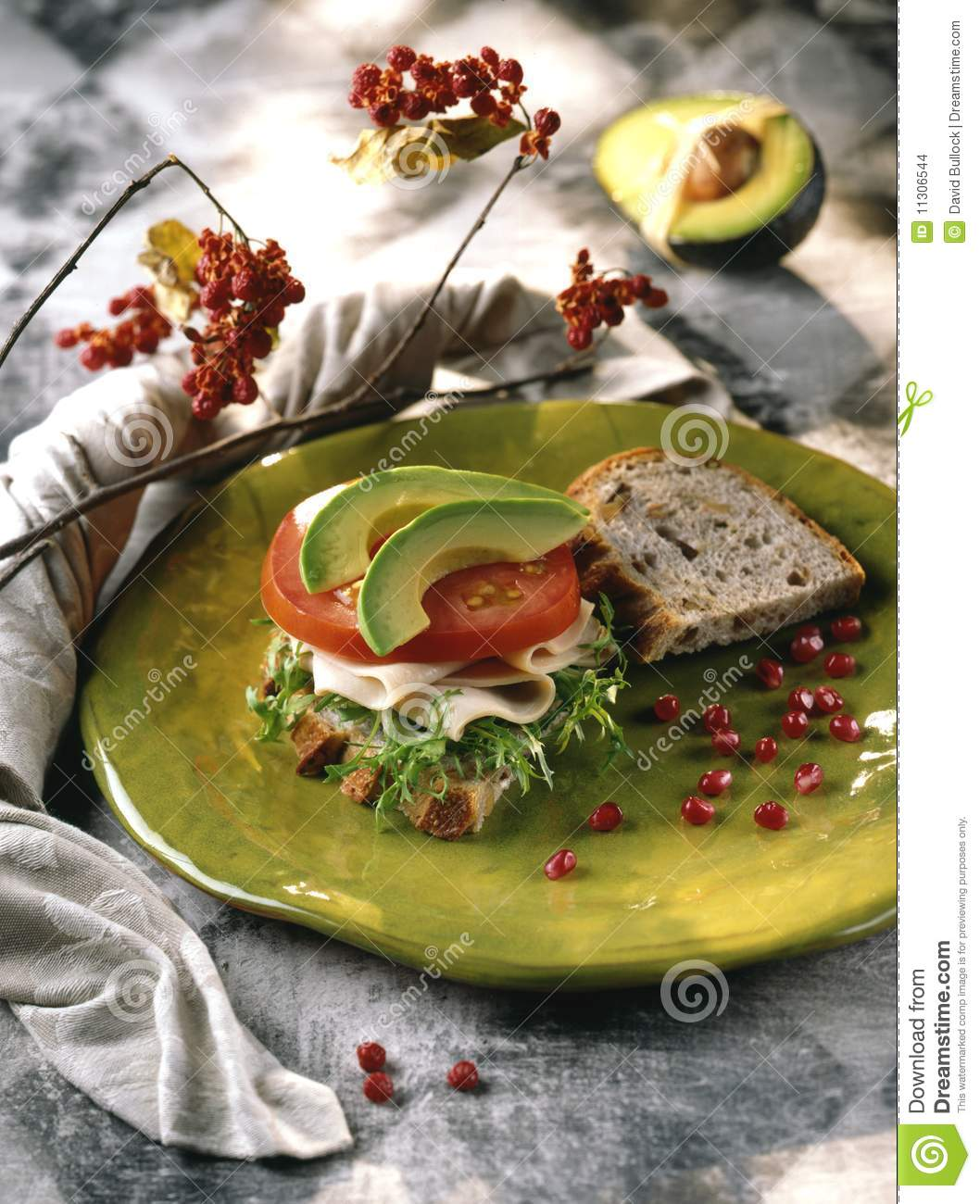 Turkey and avocado sandwich on green plate with arugula and tomato.