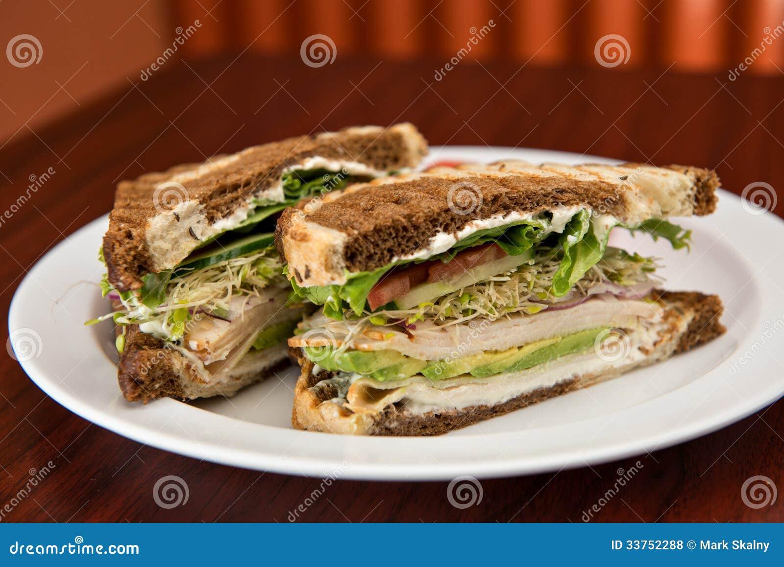 deli classic turkey sandwich with avocado on rye bread.