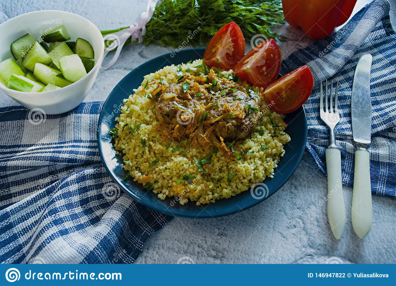 Turkish bulgur pilaf with meatballs and greens. Tasty homemade food close up