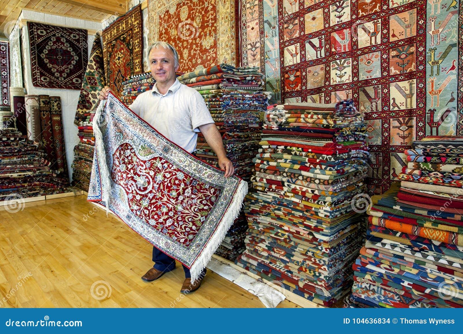 A Turkish Carpet Seller Displays Rug In Shop The Old Town Of Kaleici
