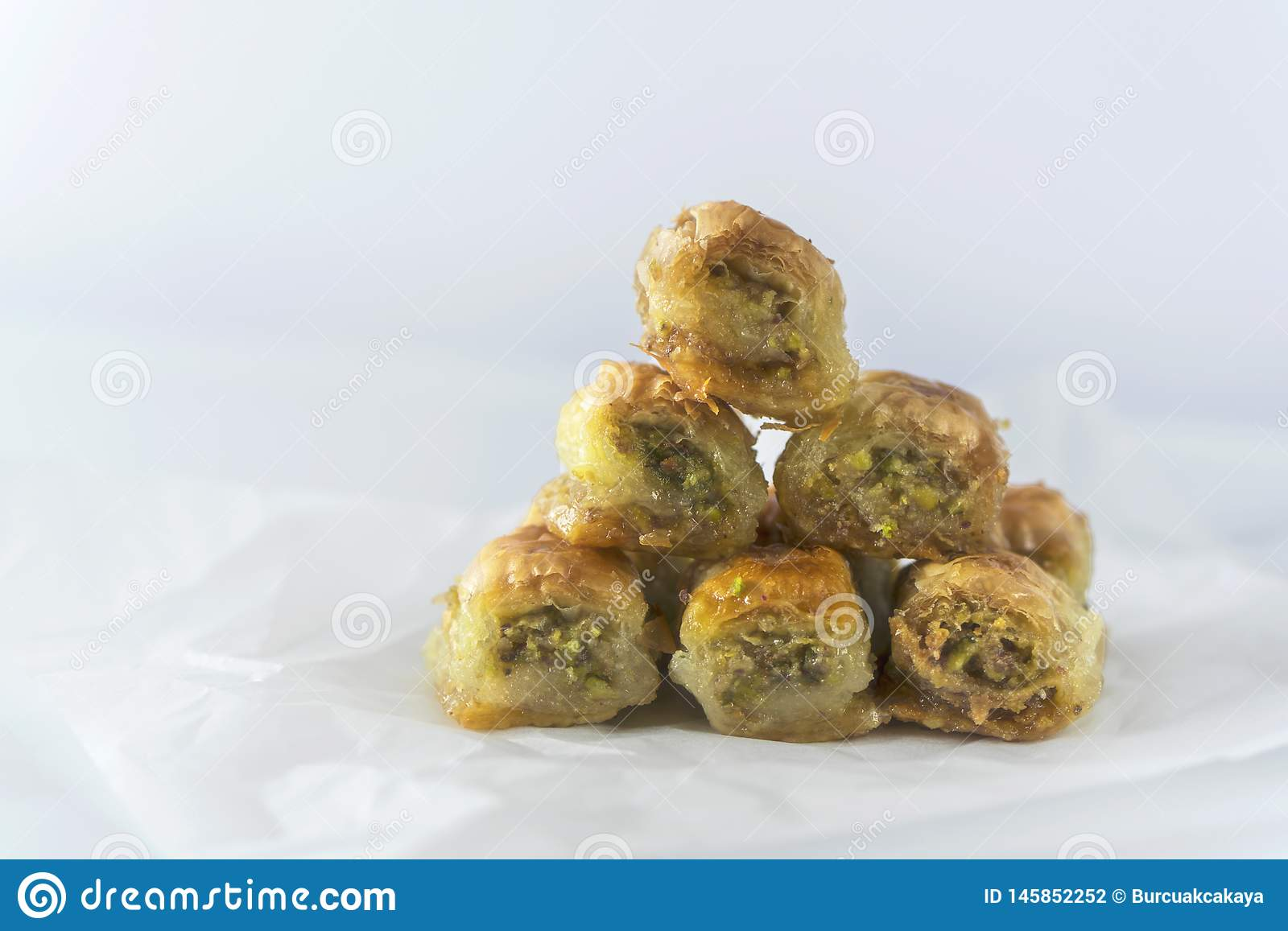 Turkish traditional dessert Baklava on a backing paper, close up, isolated