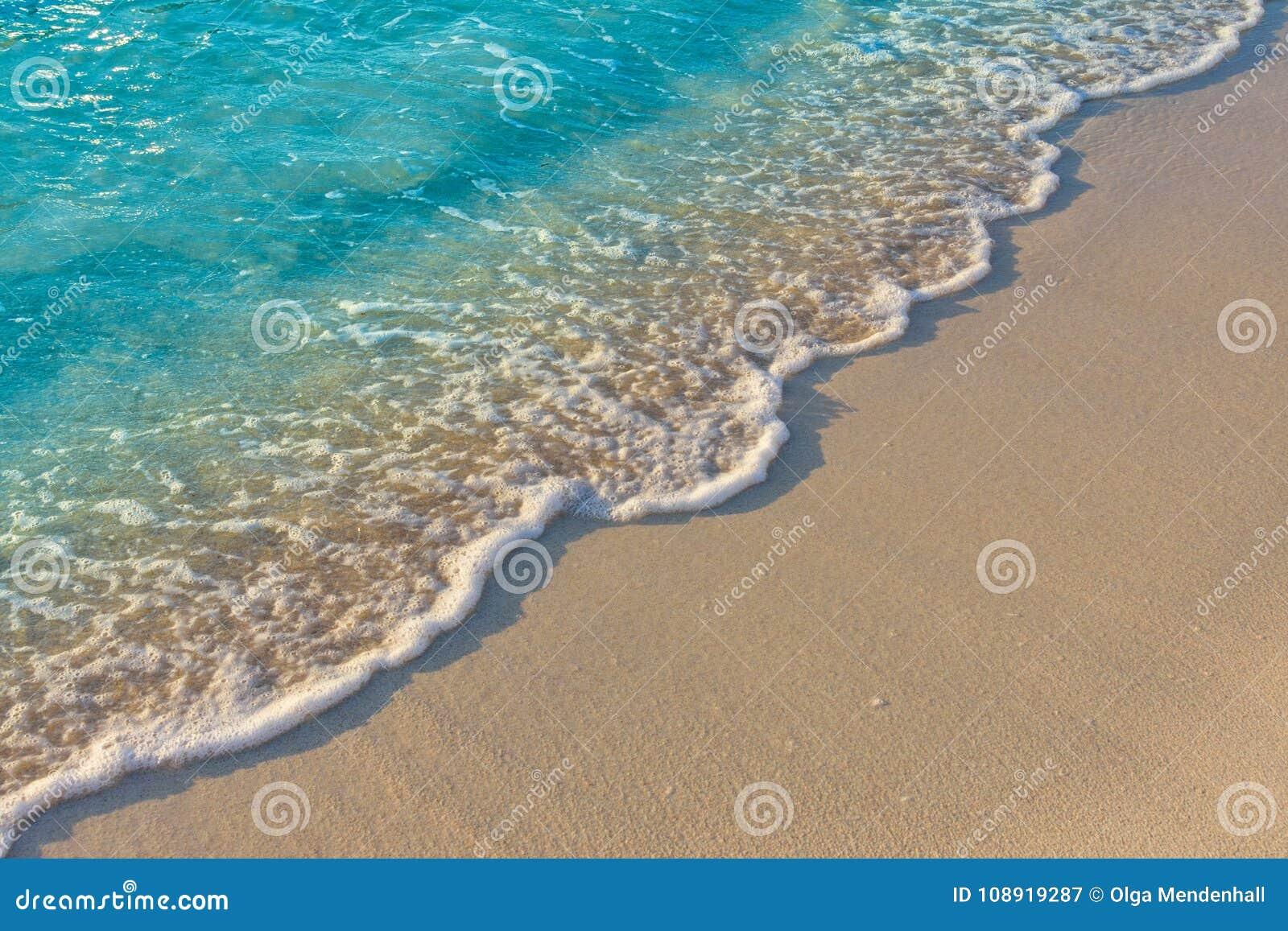 Turkooise blauwe oceaangolf op zandig strand Achtergrond, Textuur
