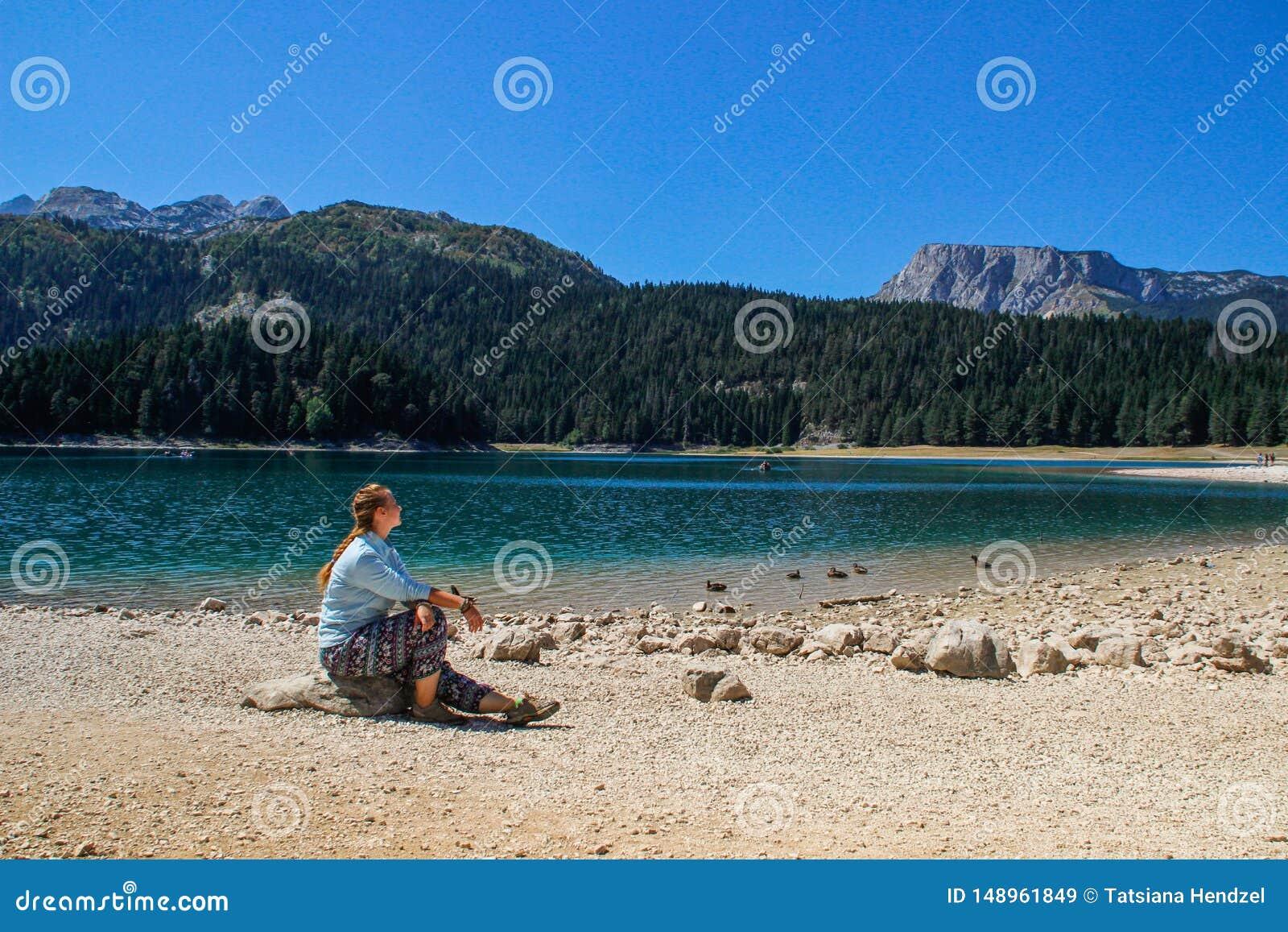 Turkosvatten av sj?n, pinjeskogen och bergen Bed?va bakgrund med naturflickaturisten som sitter p? stranden