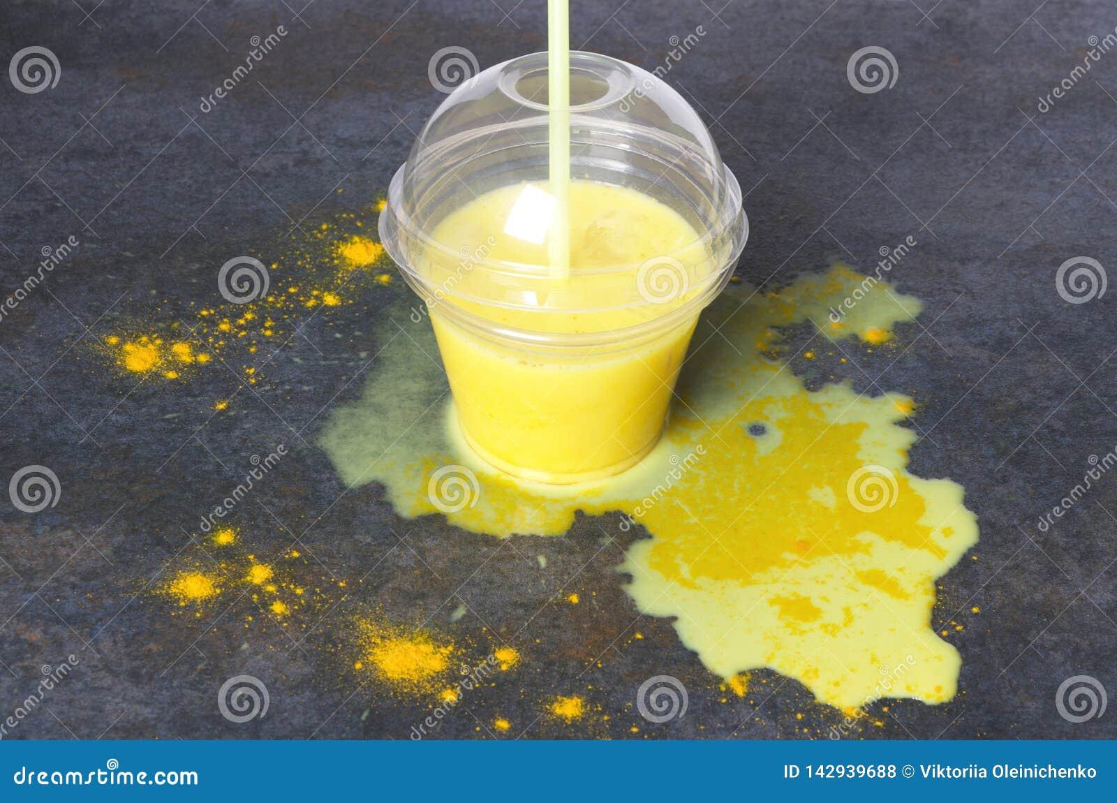 Turmeric latte στο σκοτεινό πίνακα Χυμένο χρυσό γάλα στον πίνακα κουζινών Φλυτζάνι του χρυσού γάλακτος