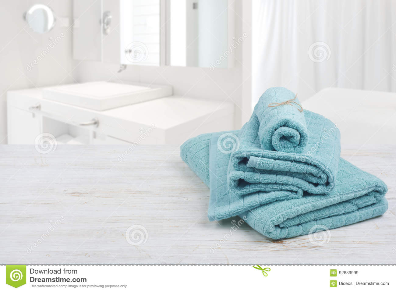Turquoise Spa Towels On Wooden Surface Over Blurred Bathroom ...