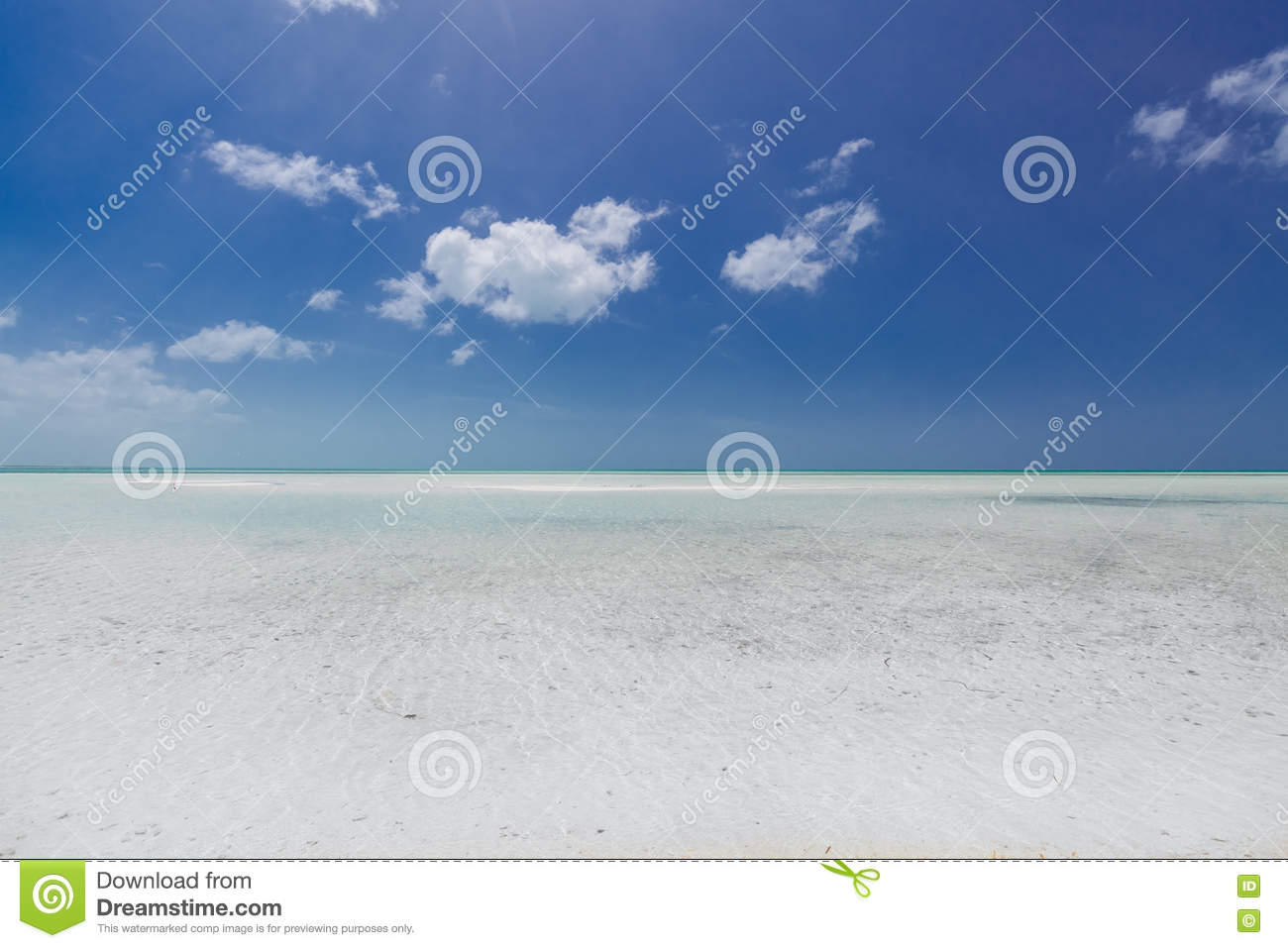 Turquoise, tranquil ocean merging with clear beautiful sky at horizon line on sunny warm day