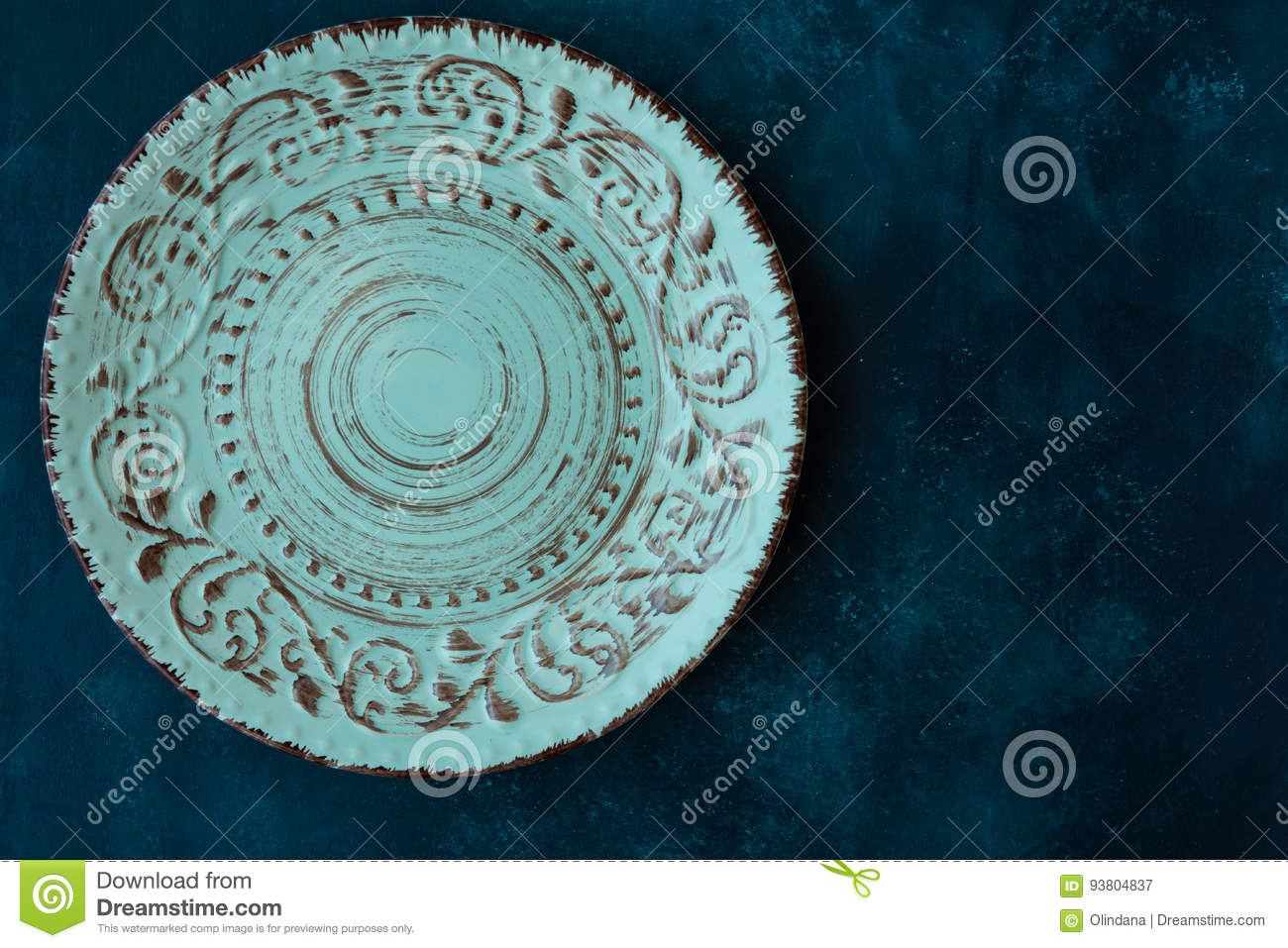 Turquoise vintage empty plate, on dark blue concrete table top, flat lay, menu template, copyspace, top view
