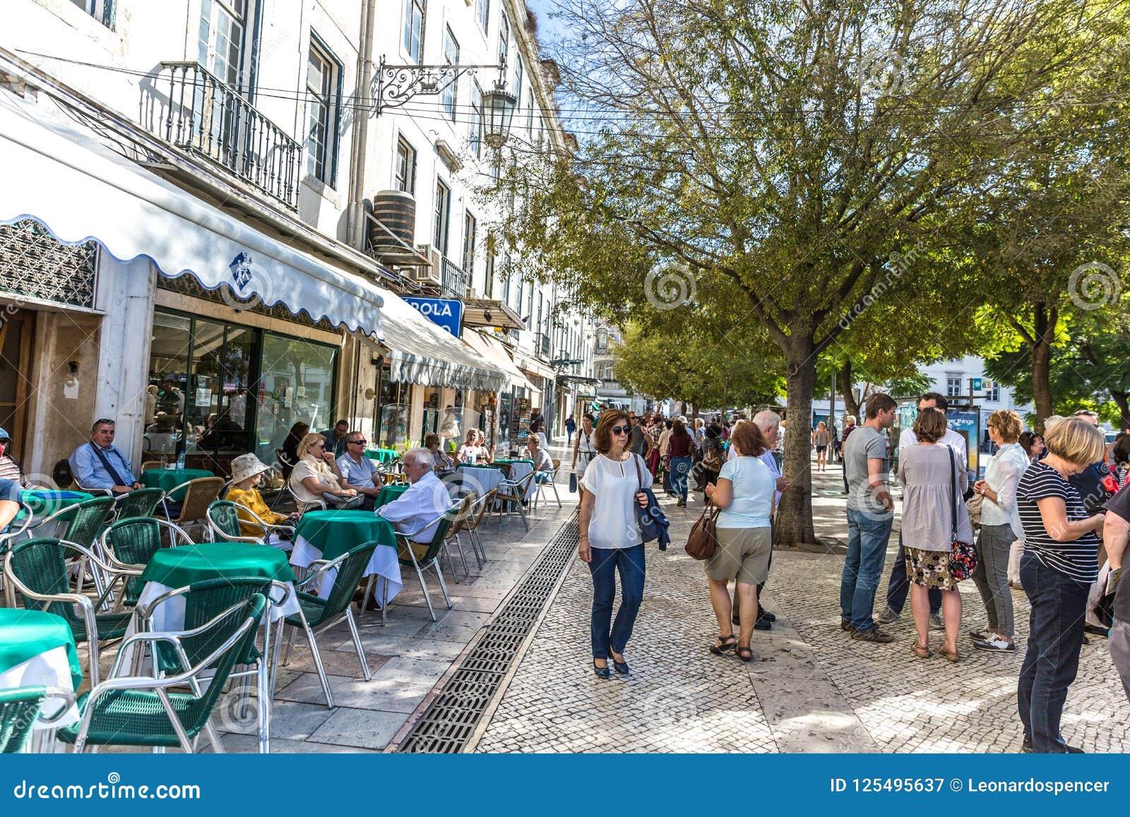 Turyści i miejscowi chodzi w tradycyjnej drodze przemian w śródmieściu, restauracjach i drzewach Lisbon, ja Lisbon, Portugalia, M