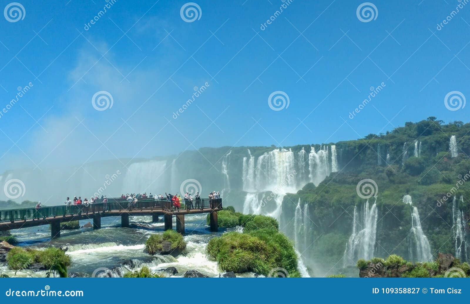 Turyści przy Iguazu spadkami, jeden światowi ` s wielcy naturalni cudy na granicie Brazylia i Argentyna,