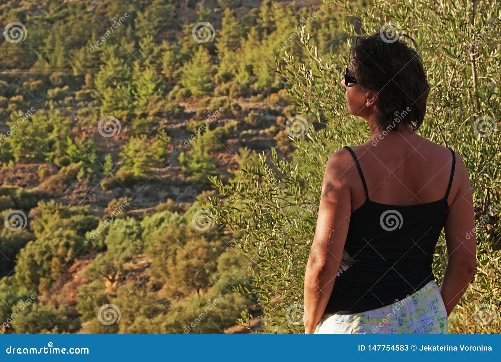 Turysty spojrzenia przy wzgórzami zakrywającymi z drzewami oliwnymi w Crete