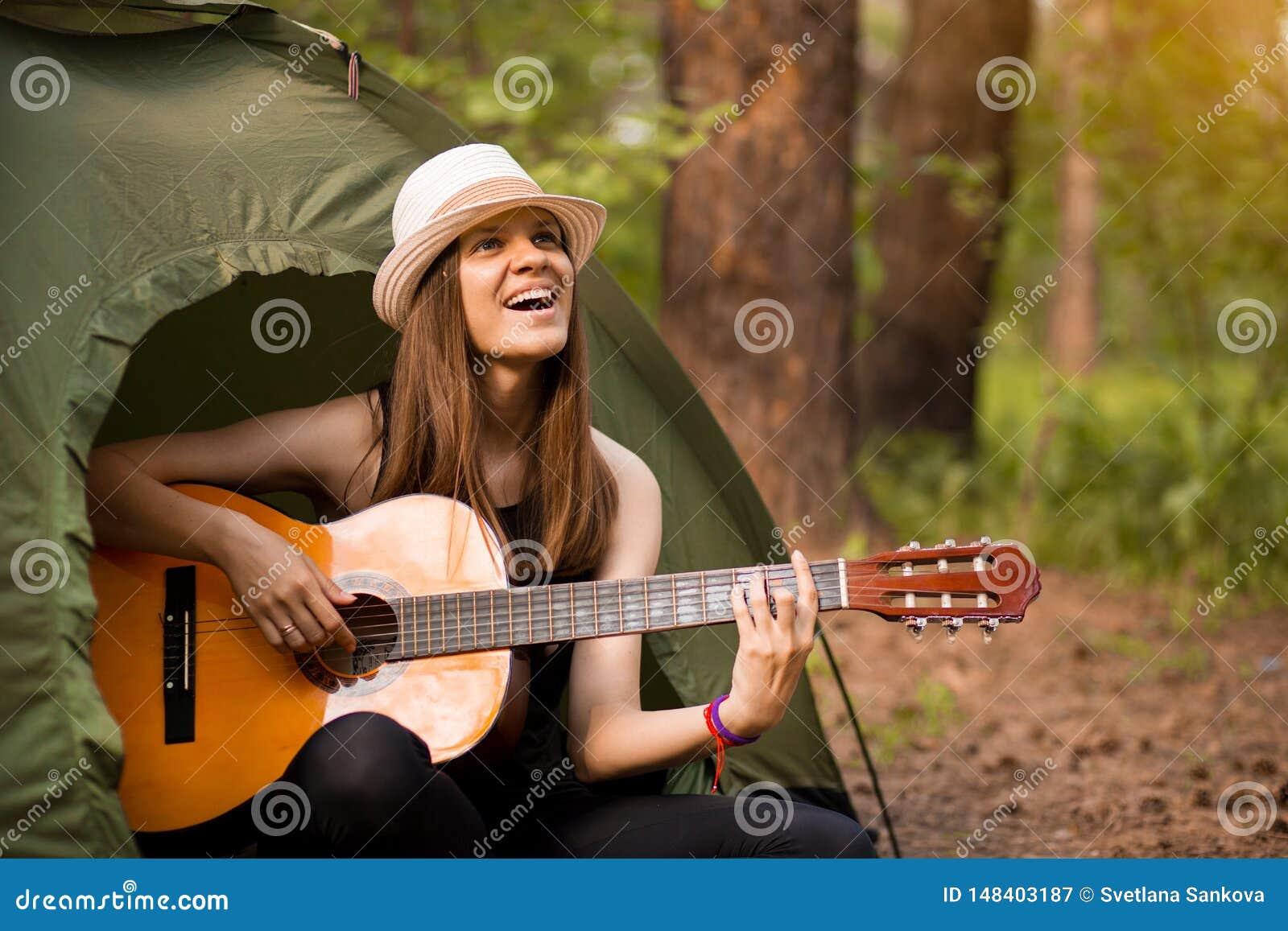 Turystyczna dziewczyna w kapeluszu siedzi w namiocie i bawi? si? gitary poj?cie Turystyka odpoczynek na naturze